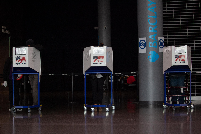 La gente emite su voto en el Barclay's Center en Brooklyn el primer día de voto anticipado, 24 de octubre, 2020.