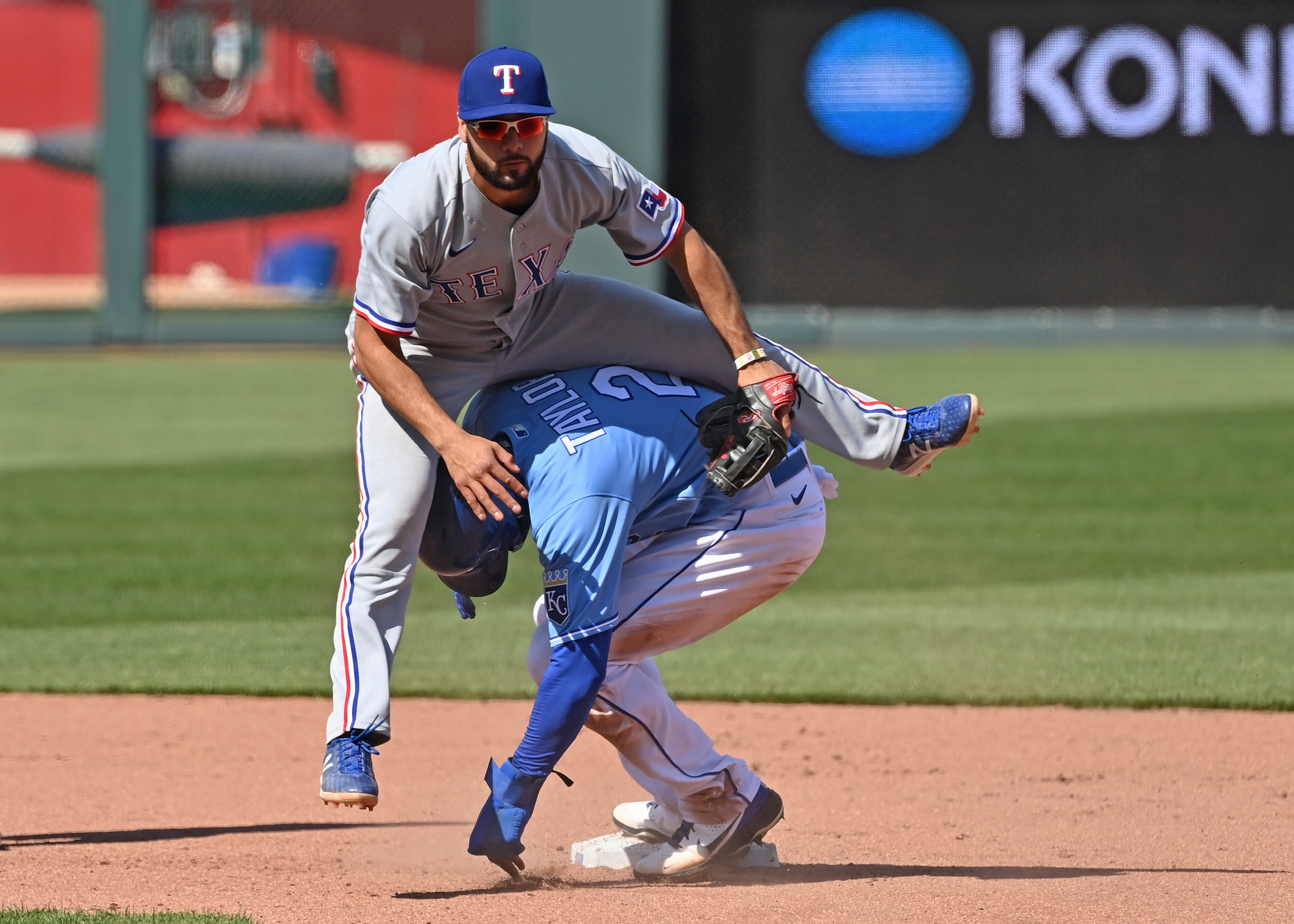 Texas Rangers short stop Isiah Kiner-Falefa (9) leaps over Kansas City Royals center fielder Michael A. Taylor (2) after forcing him out at second base during the seventh inning at Kauffman Stadium. Mandatory Credit: Peter Aiken