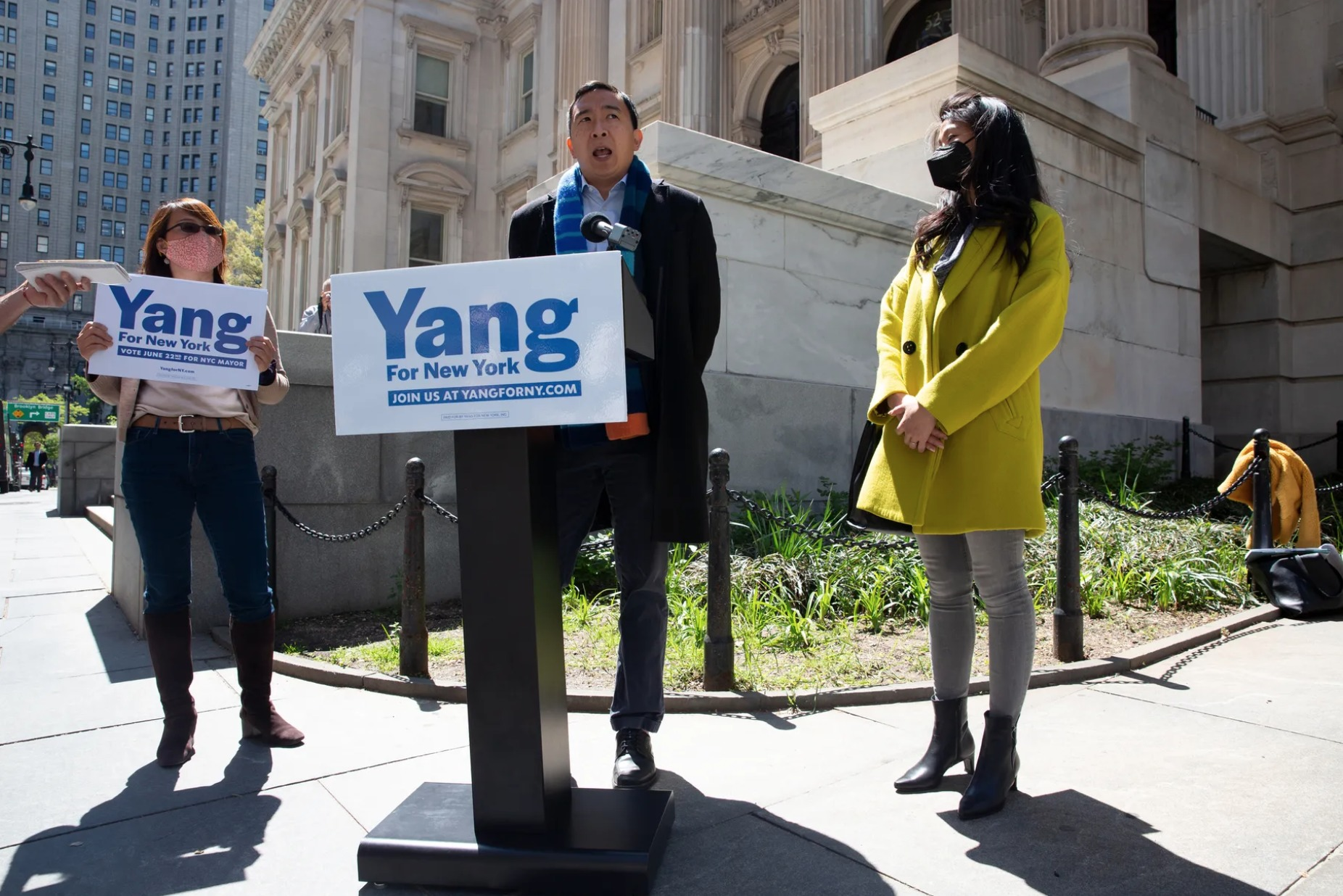 NYC mayoral candidate Andrew Yang speaks at a podium that bears his campaign sign, with a woman holding his campaign sign on his left and a woman wearing a yellow coat to his right.