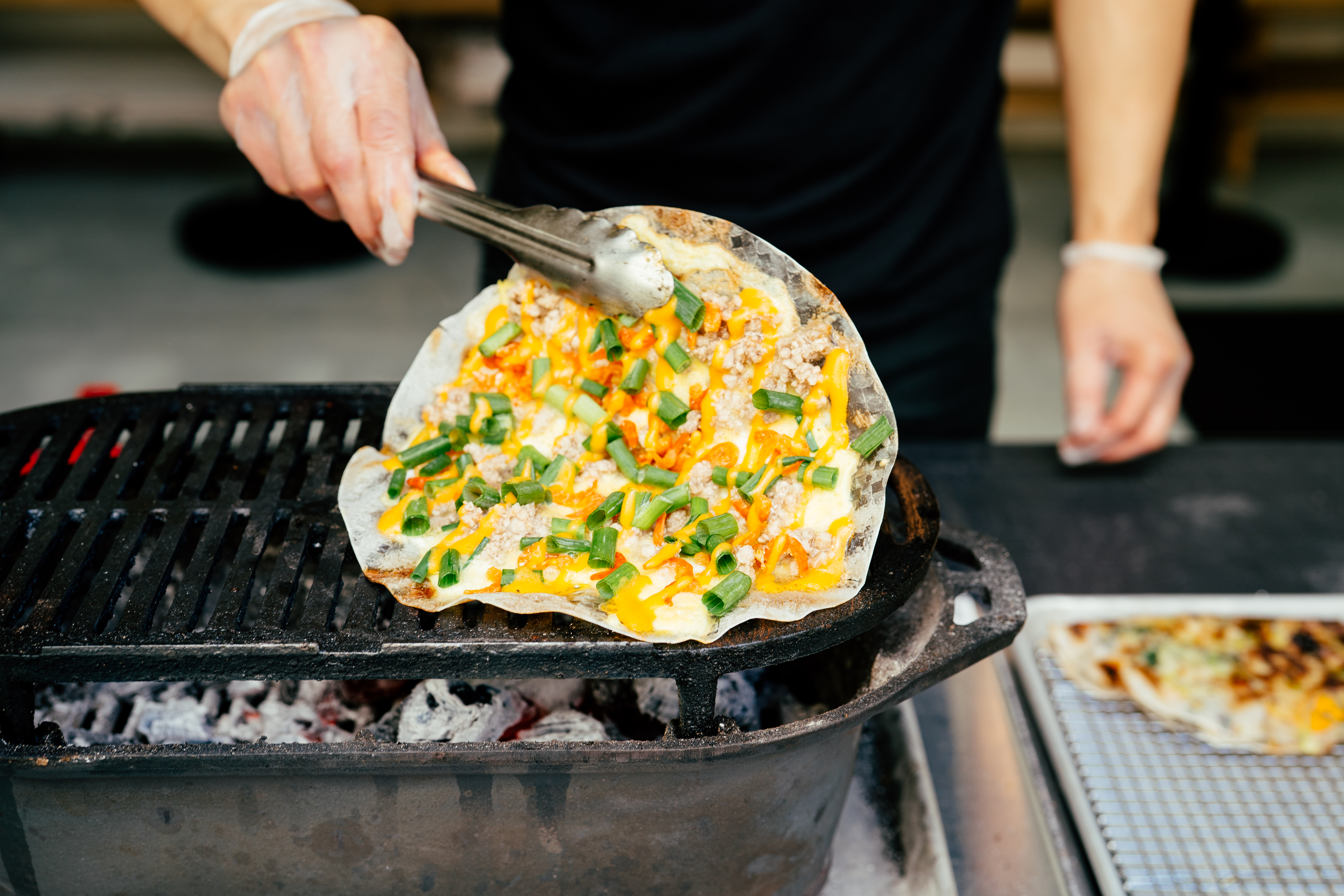 A man holds up a crackly rice cracker, covered in yellow egg, green onions, and crumbles of meat, over a small charcoal grill. This is from the Berlu pop-up featuring bánh tráng nướng