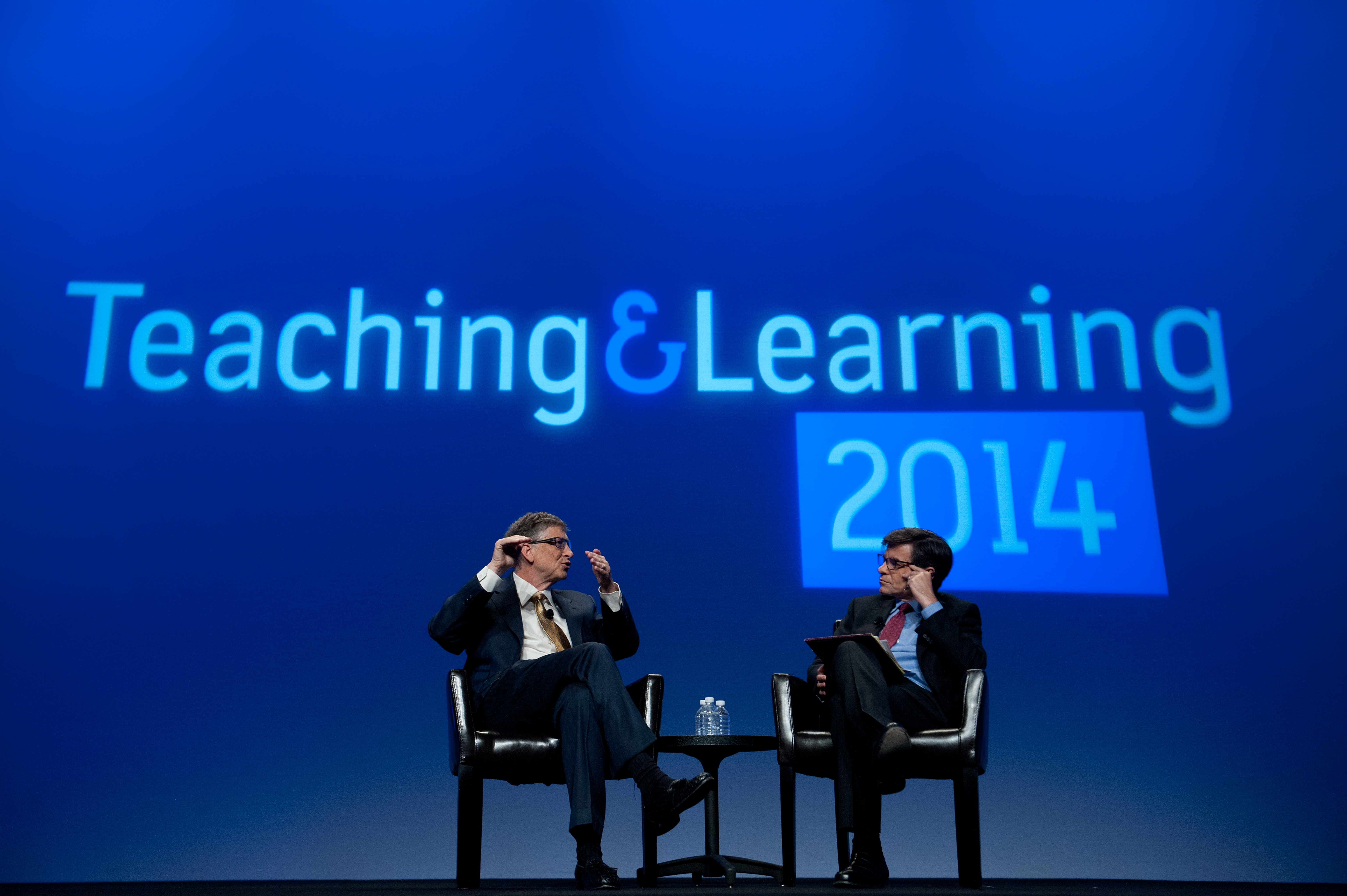 """(Left to right) Microsoft founder Bill Gates and television host George Stephanopoulos sit face-to-face on stage during an interview in front of a blue projected backdrop that reads """"Teaching & Learning 2014""""."""