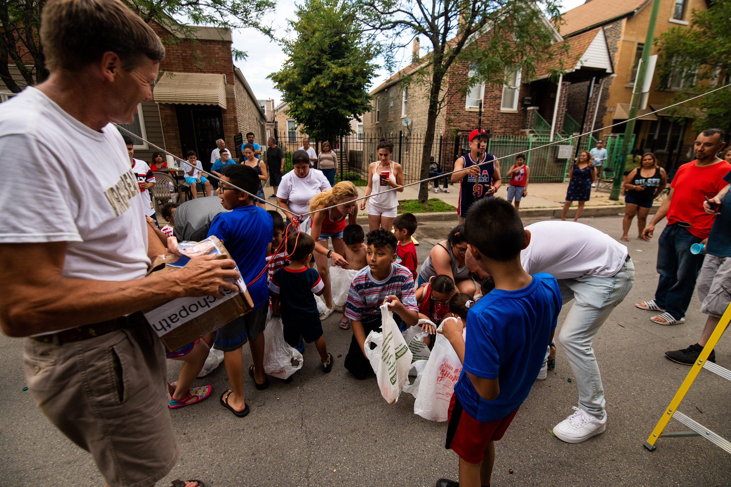 Children gather round to gather the candy that fell from a homemade Donald Trump Piñata at a Fourth of July block party in the Pilsen neighborhood, Thursday, July 4, 2019, in Chicago