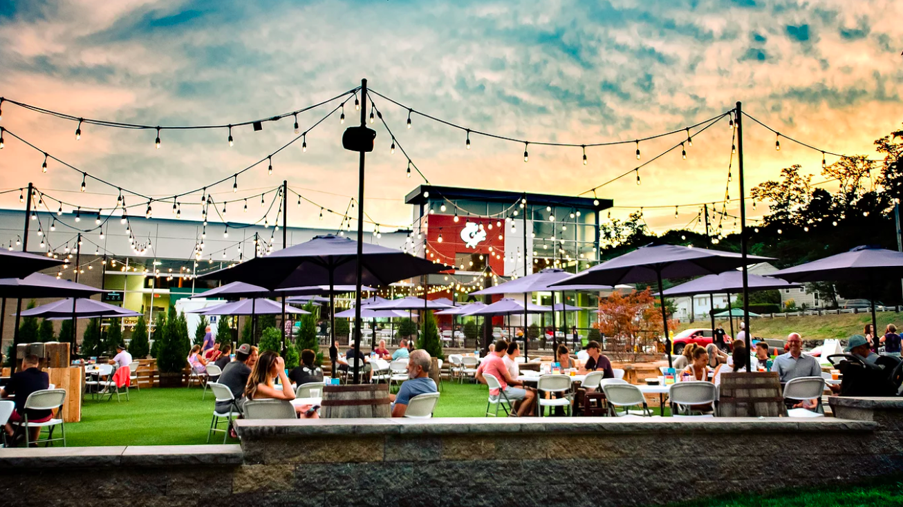 Sunset view of a large brewery patio on green turf, with blue umbrellas above each table