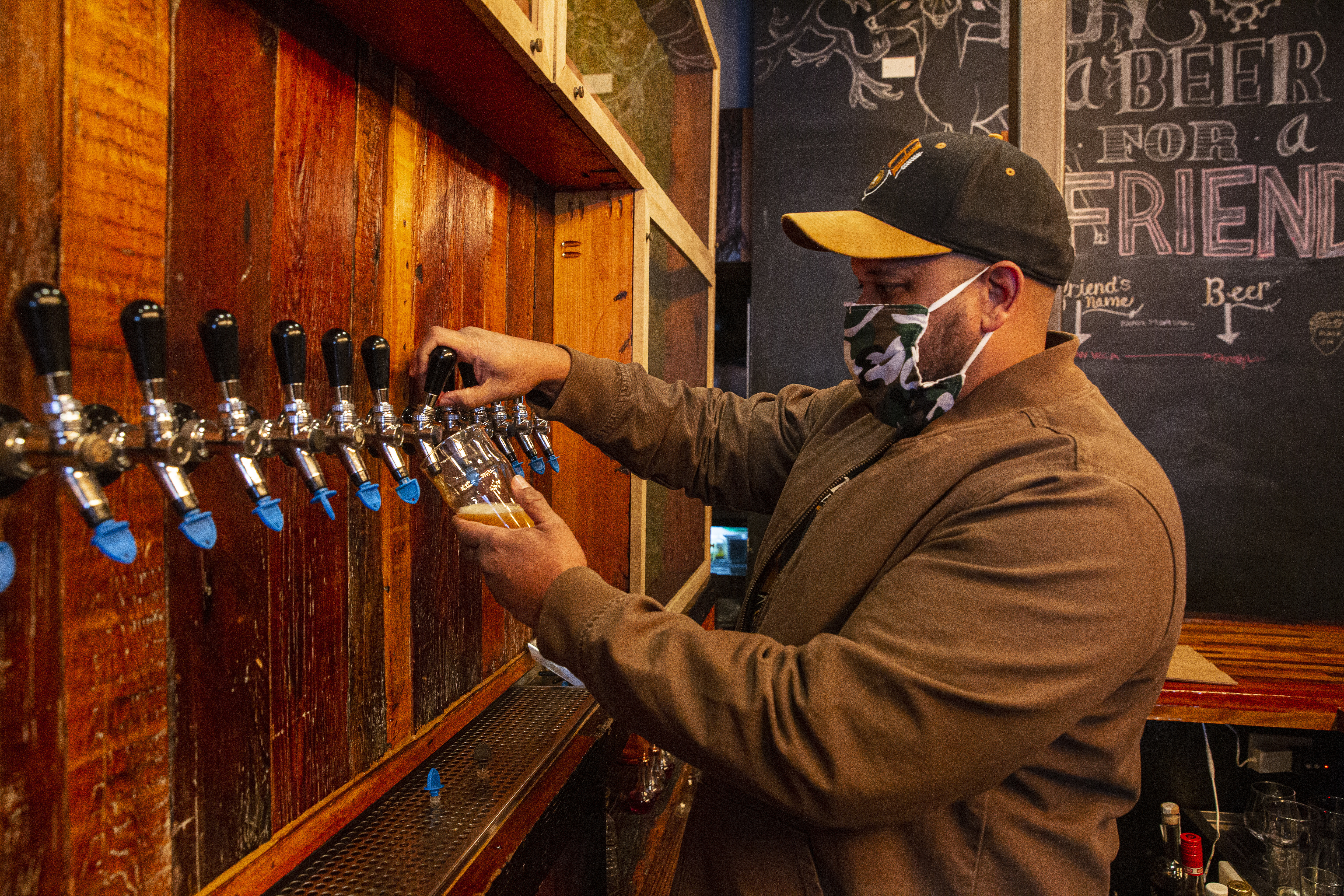 A man wearing a mask pours beer into a class out of a tap.