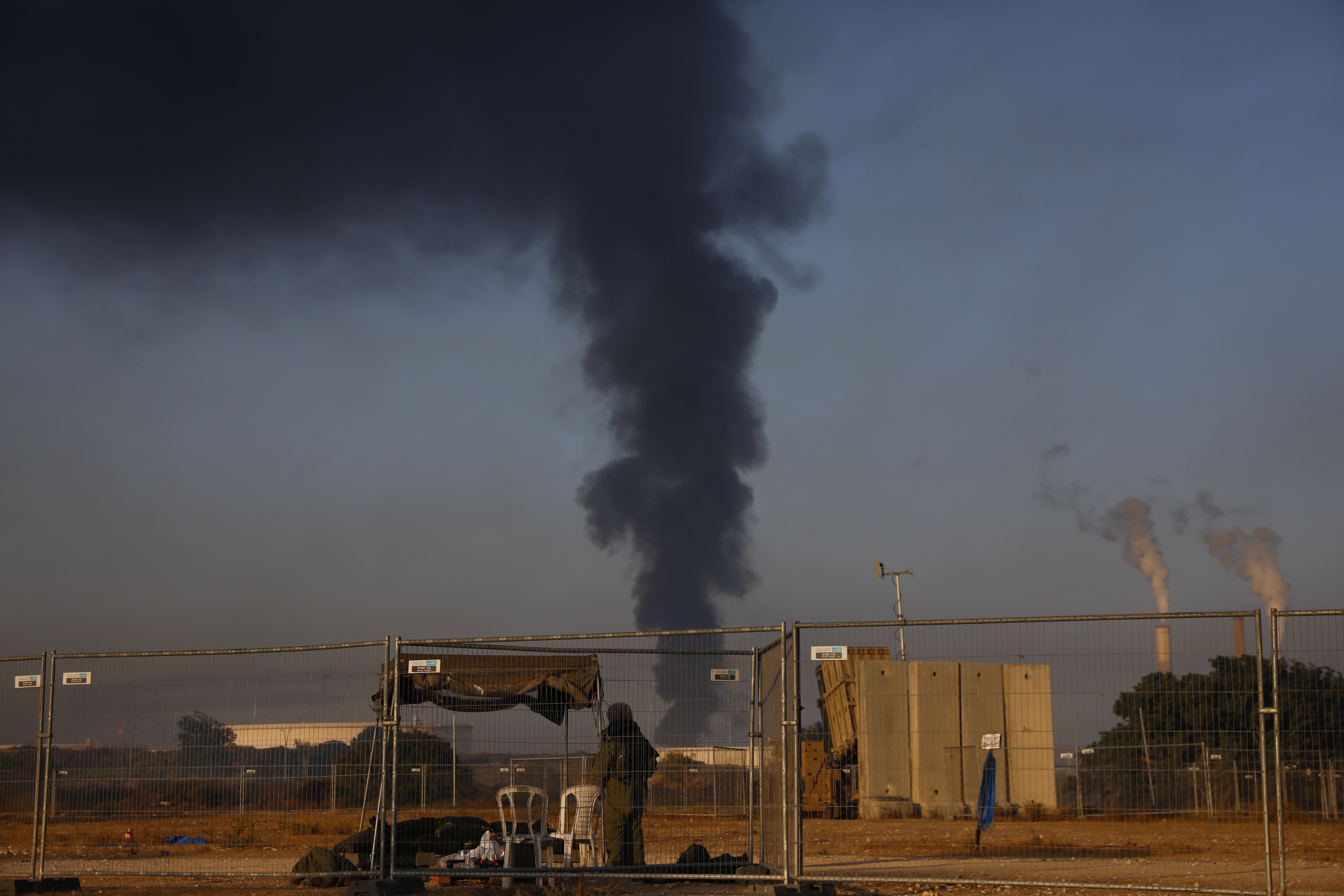 An Israeli soldier stands guard next to an Iron Dome air defense system as smoke rises from an oil tank on fire after it was hit by a rocket fired from Gaza Strip, near the town of Ashkelon, Israel.