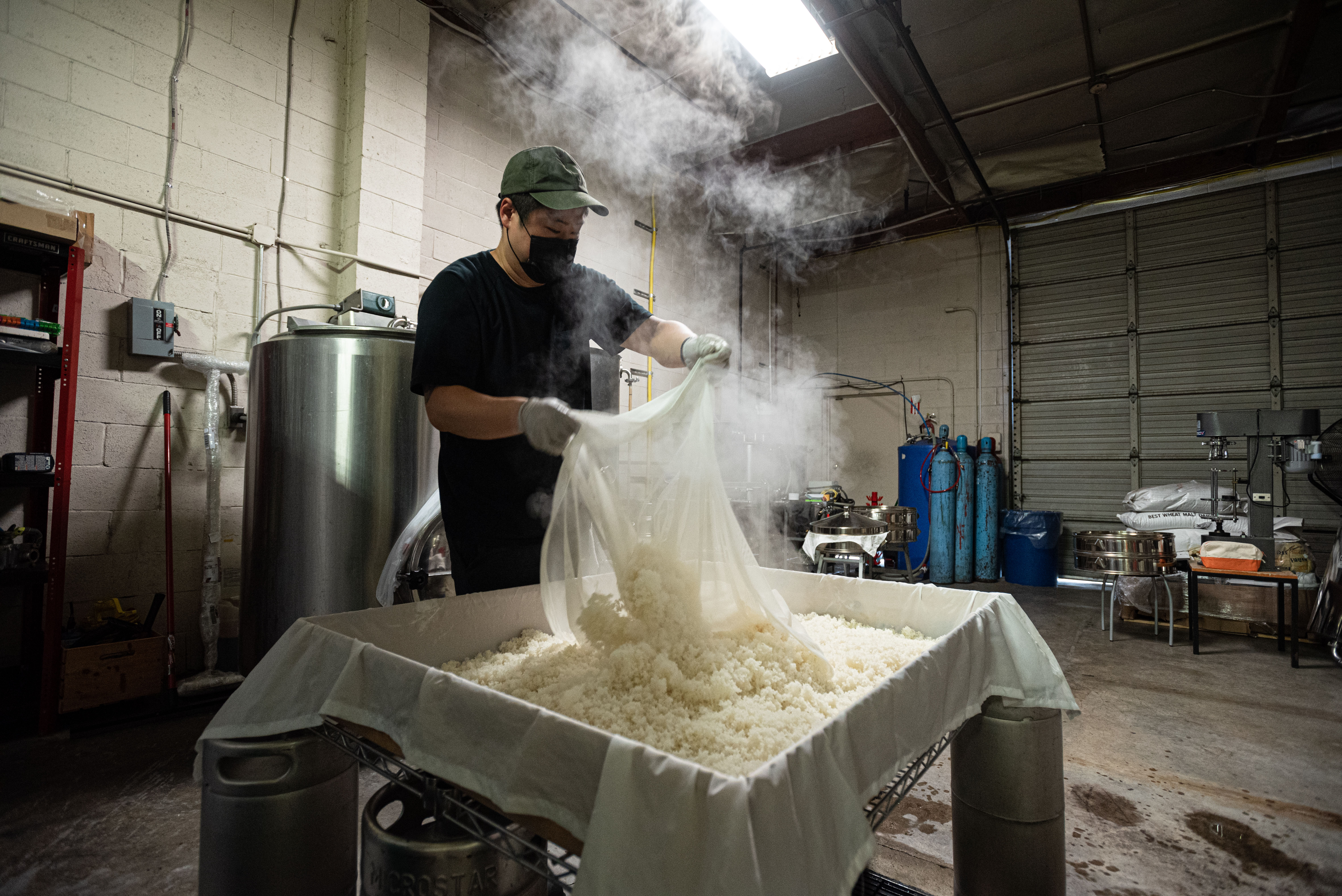 James Jin takes out cooked rice to cool at Nova Brewing in Covina, California.