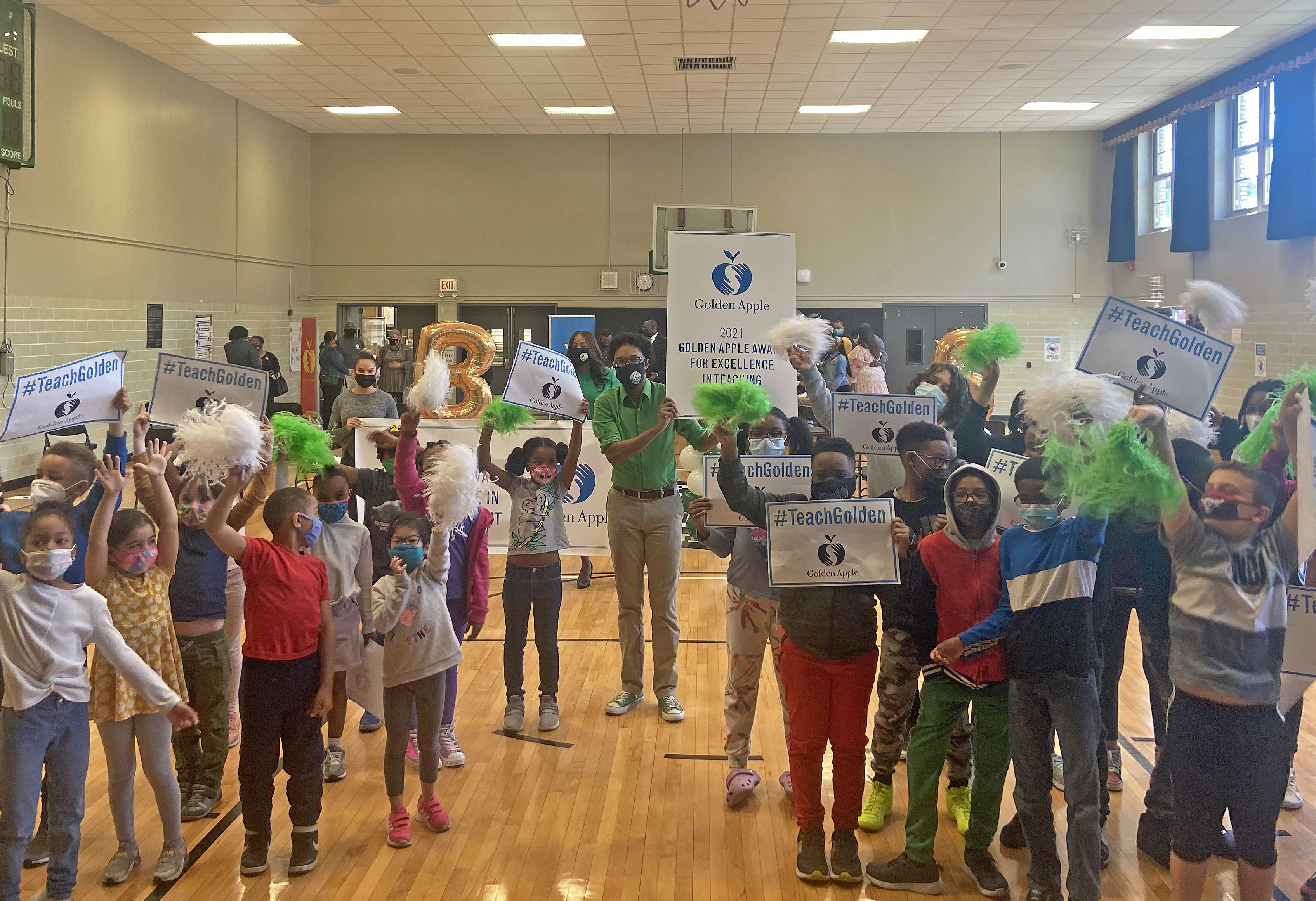 Teacher Reggie Spears (green shirt) surrounded by some of his students at Bronzeville Classical Elementary School after being surprised with his Golden Apple award on Thursday, May 13, 2021.