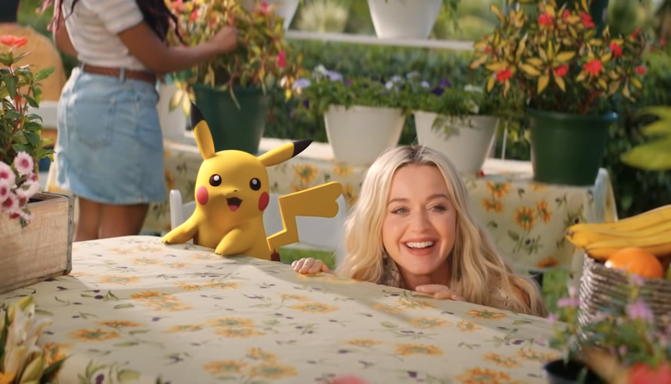 """Katy Perry and Pikachu crouch behind table in the music video for """"Electric."""""""
