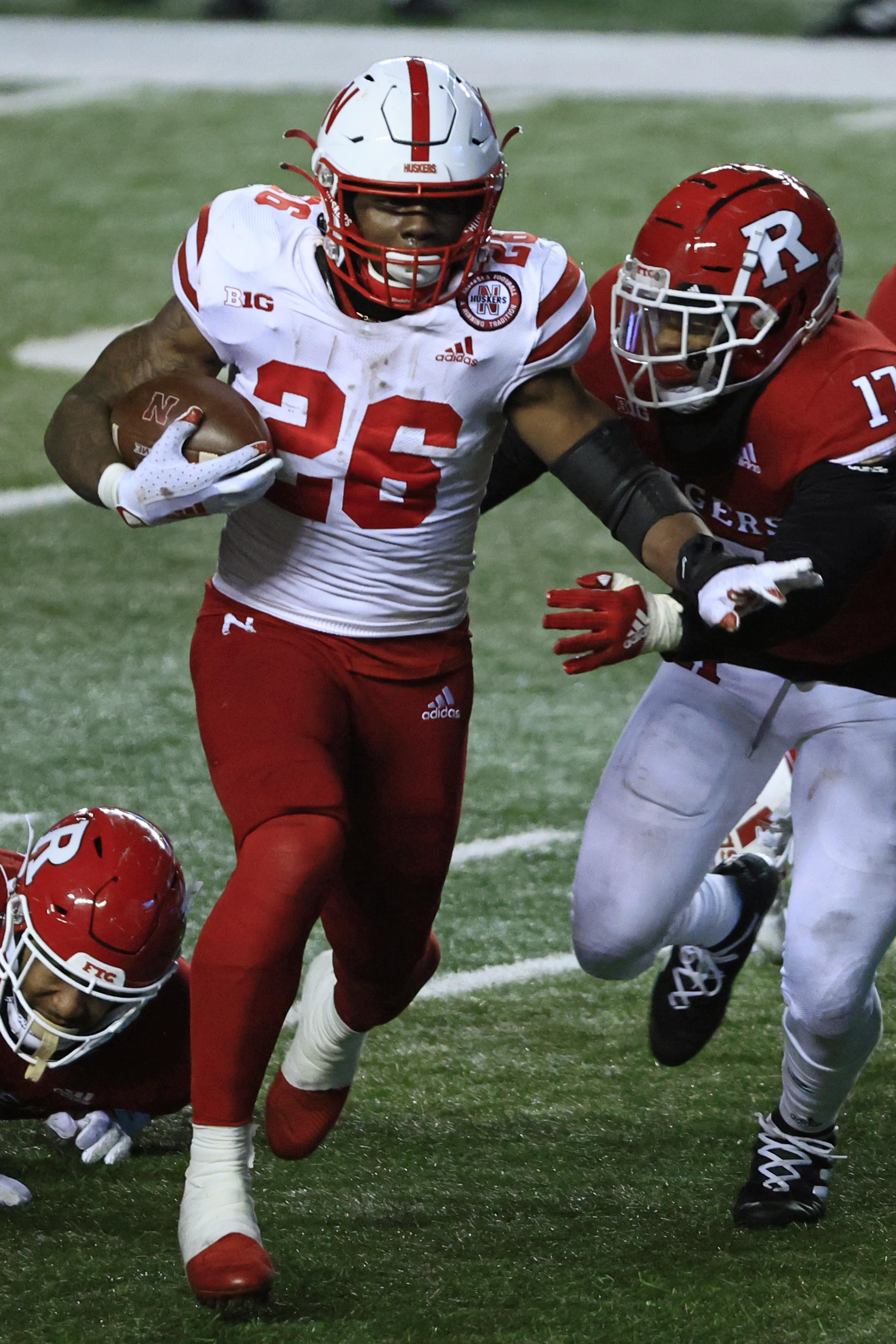 2020年12月18日,在新泽西州皮斯卡塔韦市的SHI体育场,内布拉斯加州剥玉米皮的26号球员德德里克·米尔斯(Dedrick Mills)与罗格斯猩红色骑士队的17号戴恩·詹宁斯(Deion Jennings)在第四节争分夺秒。内布拉斯加州以28比21击败罗格斯大学。