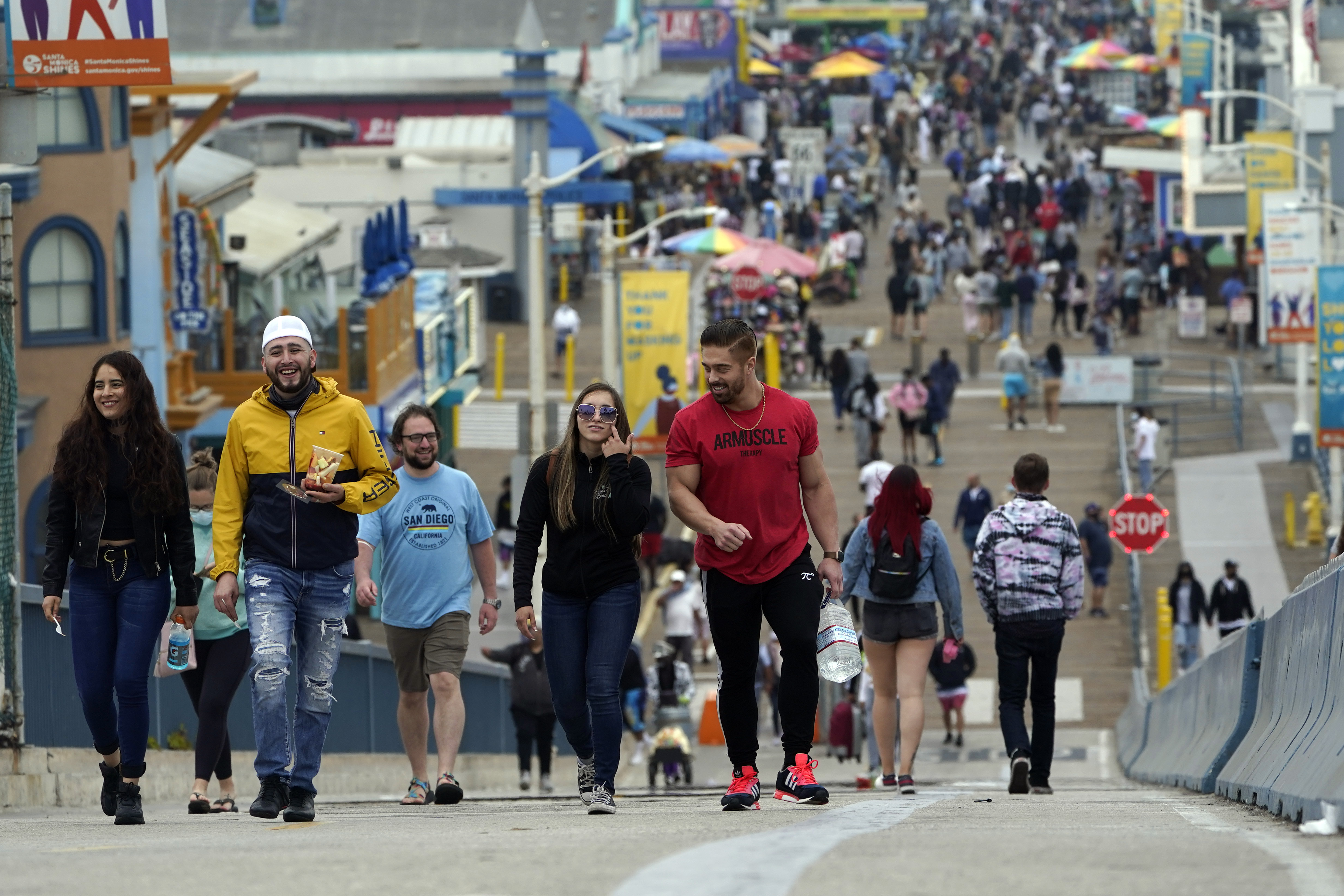 In this May 13, 2021, file photo, May 13, 2021, visitors walk without masks on the pier in Santa Monica, Calif. A number of states immediately embraced new guidelines from the CDC that say fully vaccinated people no longer need to wear masks indoors or out in most situations. But other states - and some businesses _ are taking a wait-and-see attitude.