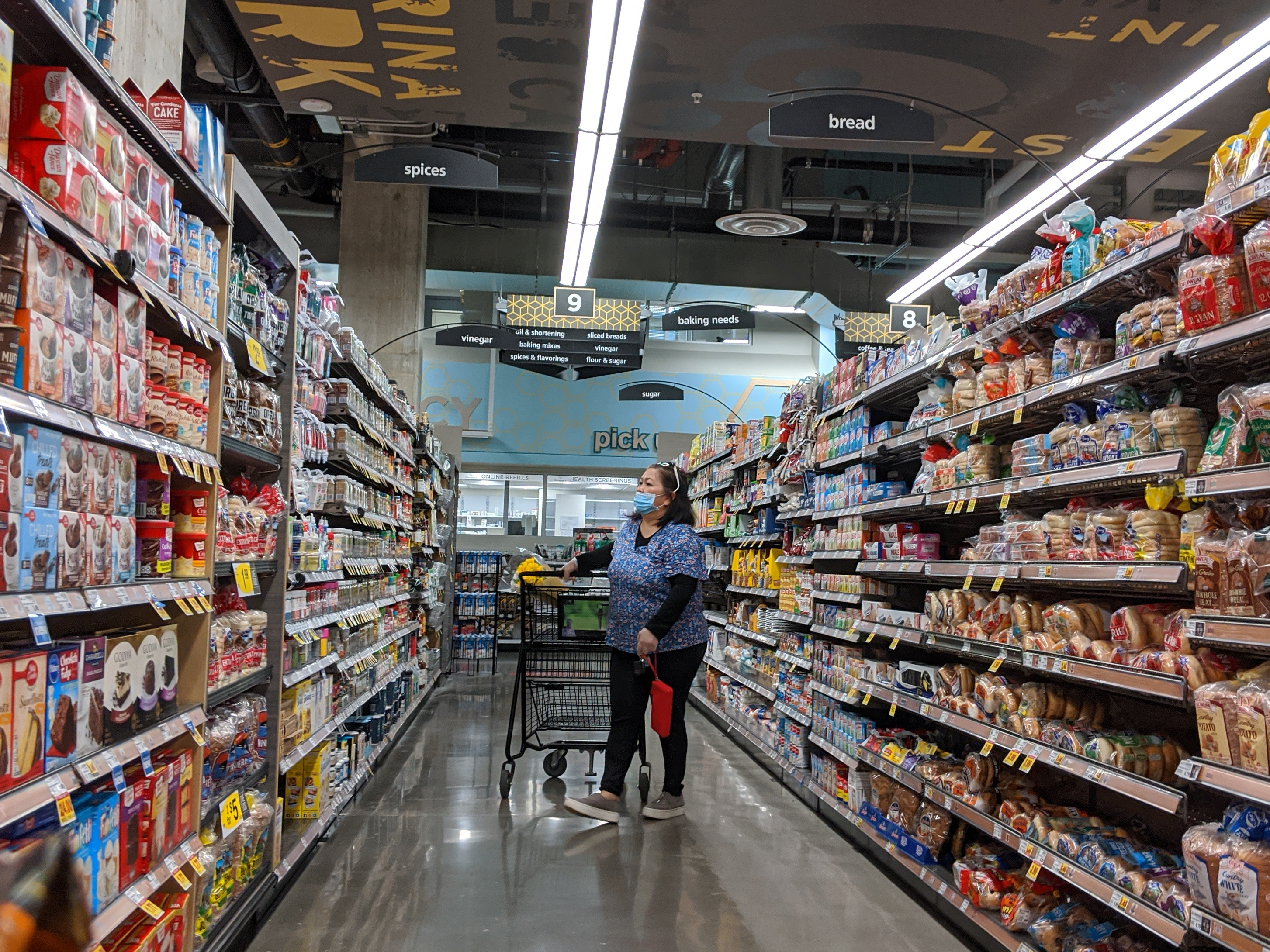 A woman wearing a blue mask stands in the center of an aisle with a shopping cart.