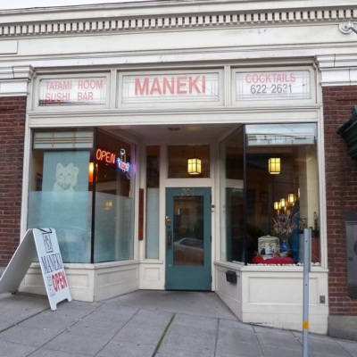 """The front of Maneki restaurant in Seattle with the restaurant's name in red lettering and a sign that says """"open"""" in the window"""