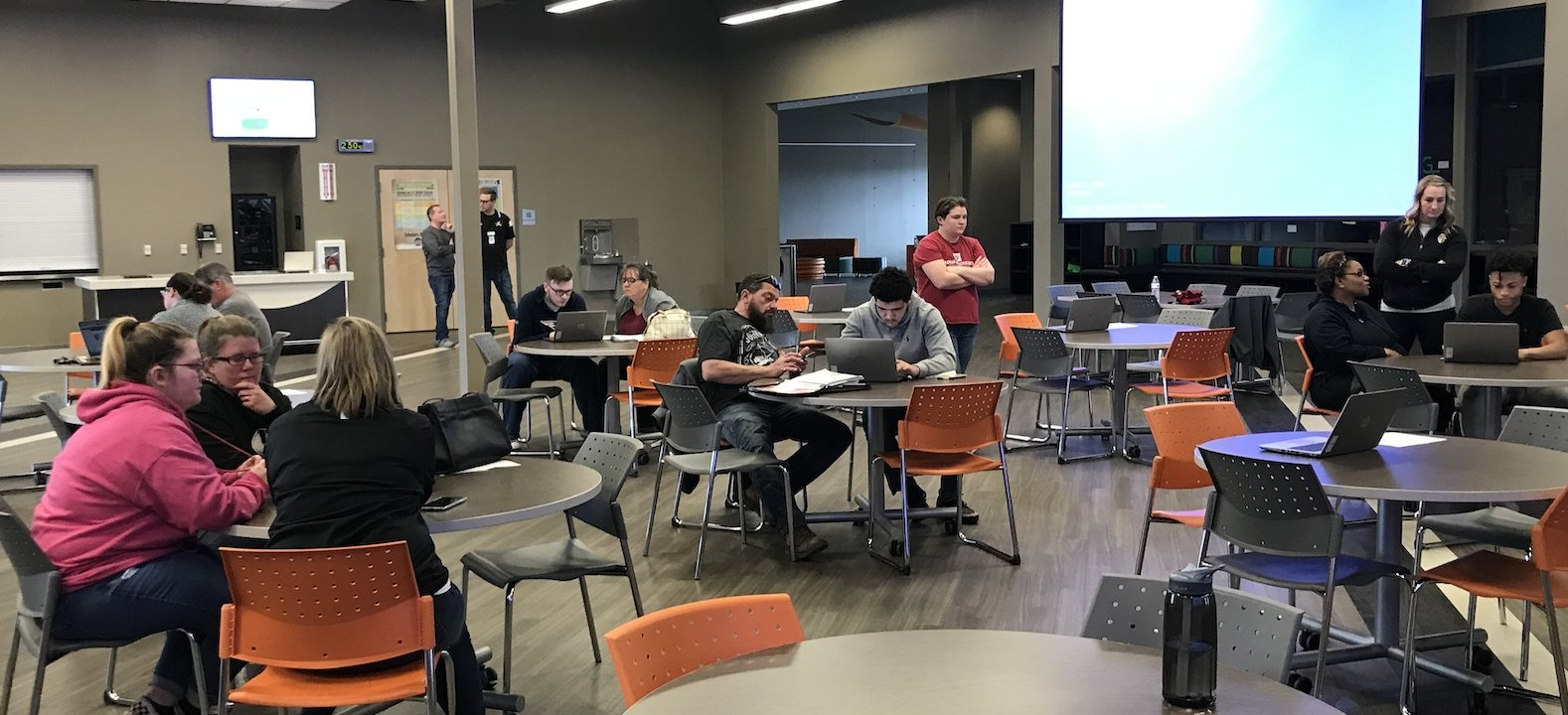 Students sit with their parents at round tables in a room, and look at laptops and papers, with some staff people standing and watching.