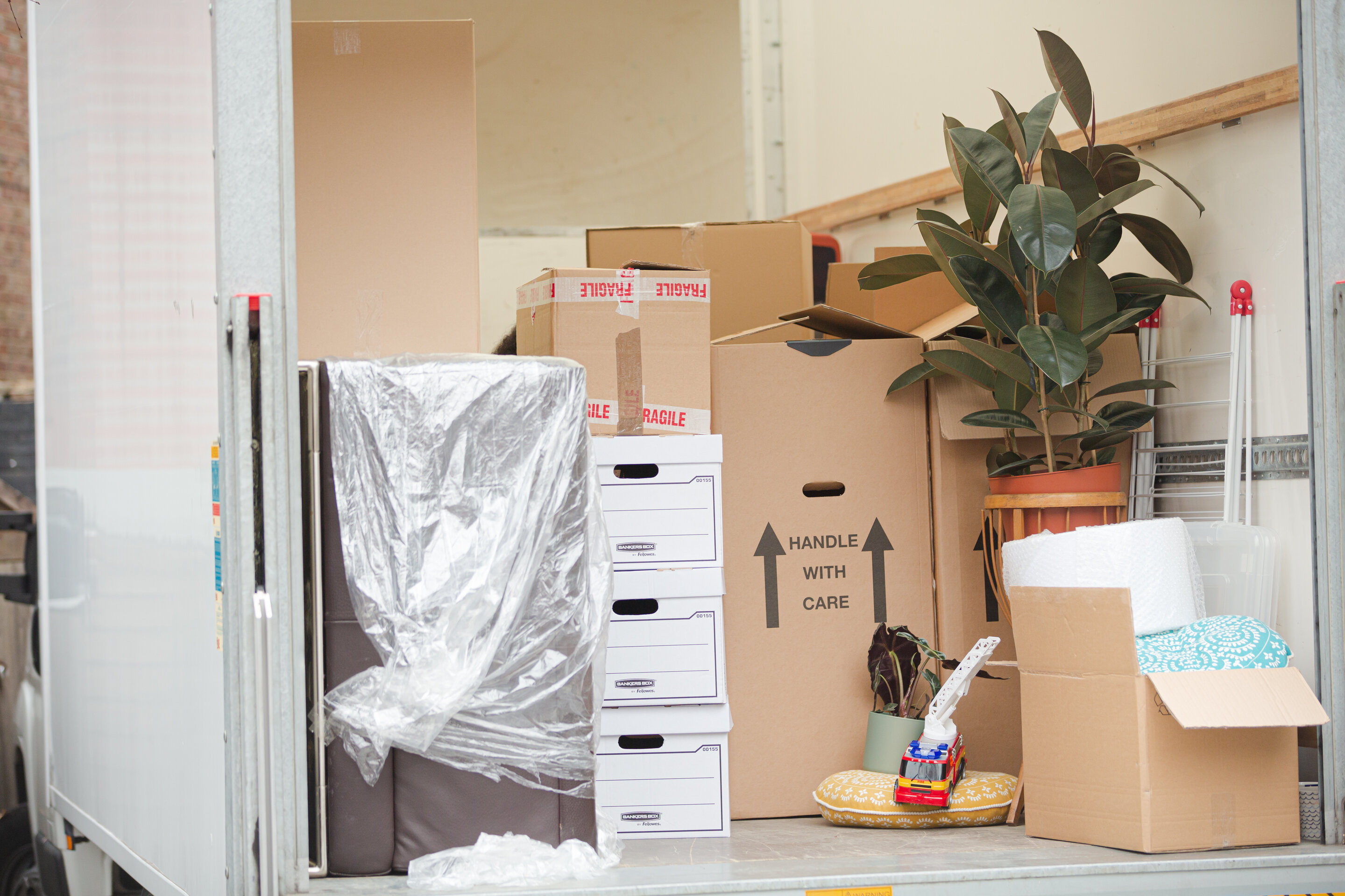 The back of an opened white moving truck with several home belongings inside like a house plant, toy truck, and several cardboard boxes.