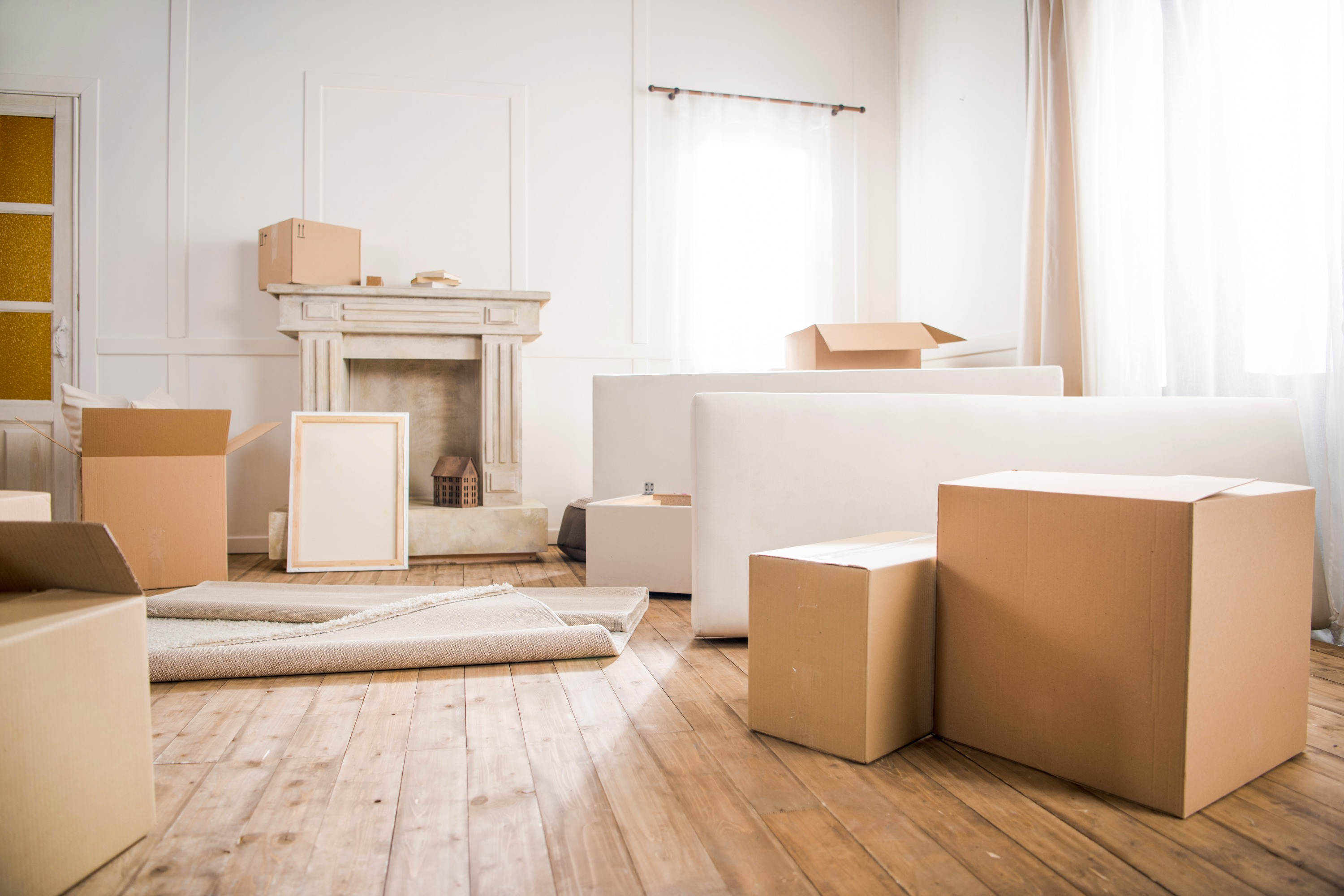 Brown cardboard moving boxes in a white room of a home with stone fireplace, white furniture, white walls, and white curtains.
