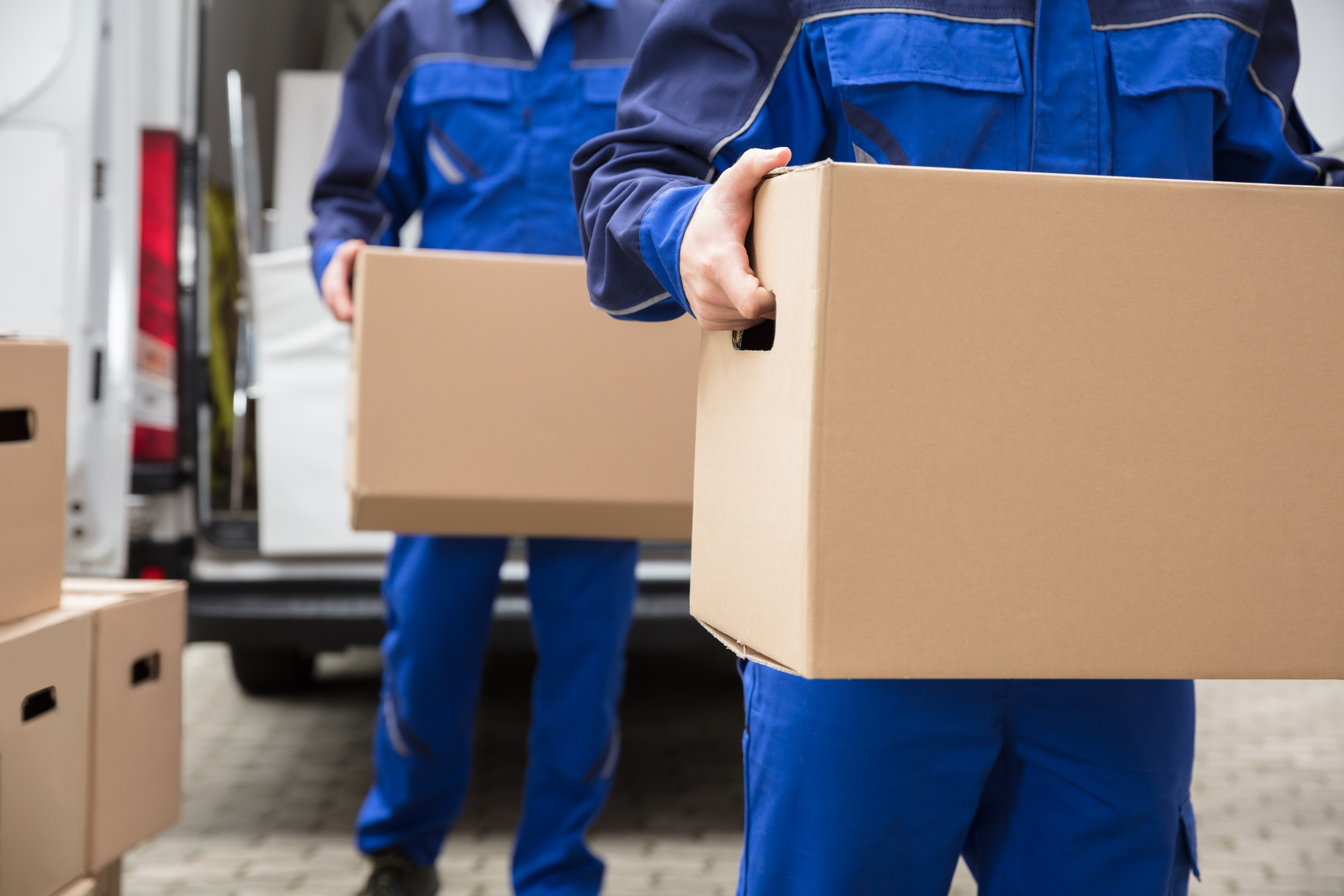 Two moving professionals wearing a dark blue uniform carry brown cardboard moving boxes away from a truck.