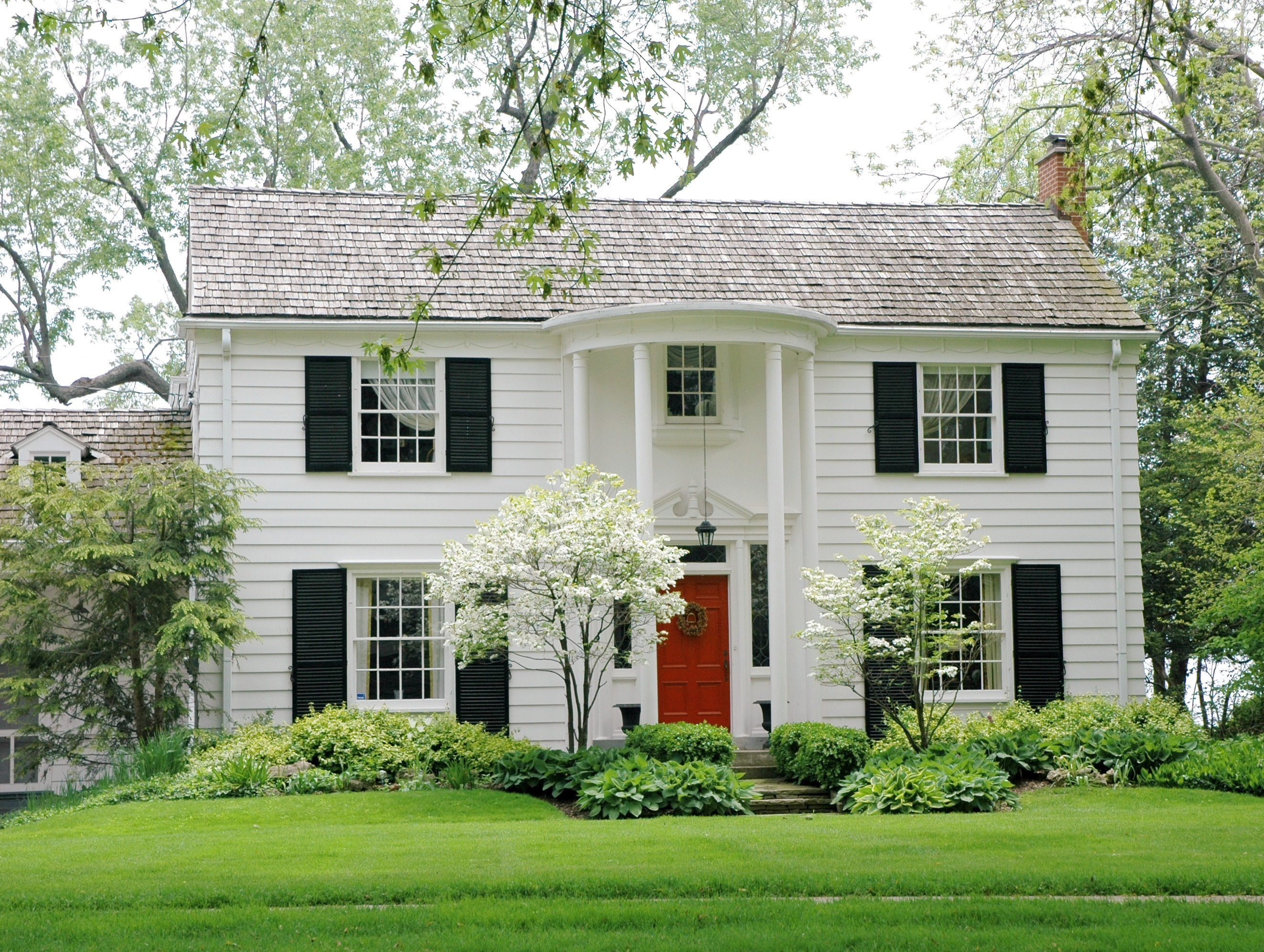 A white colonial house with red front door, black shutters, tall white columns, and bright green front yard.