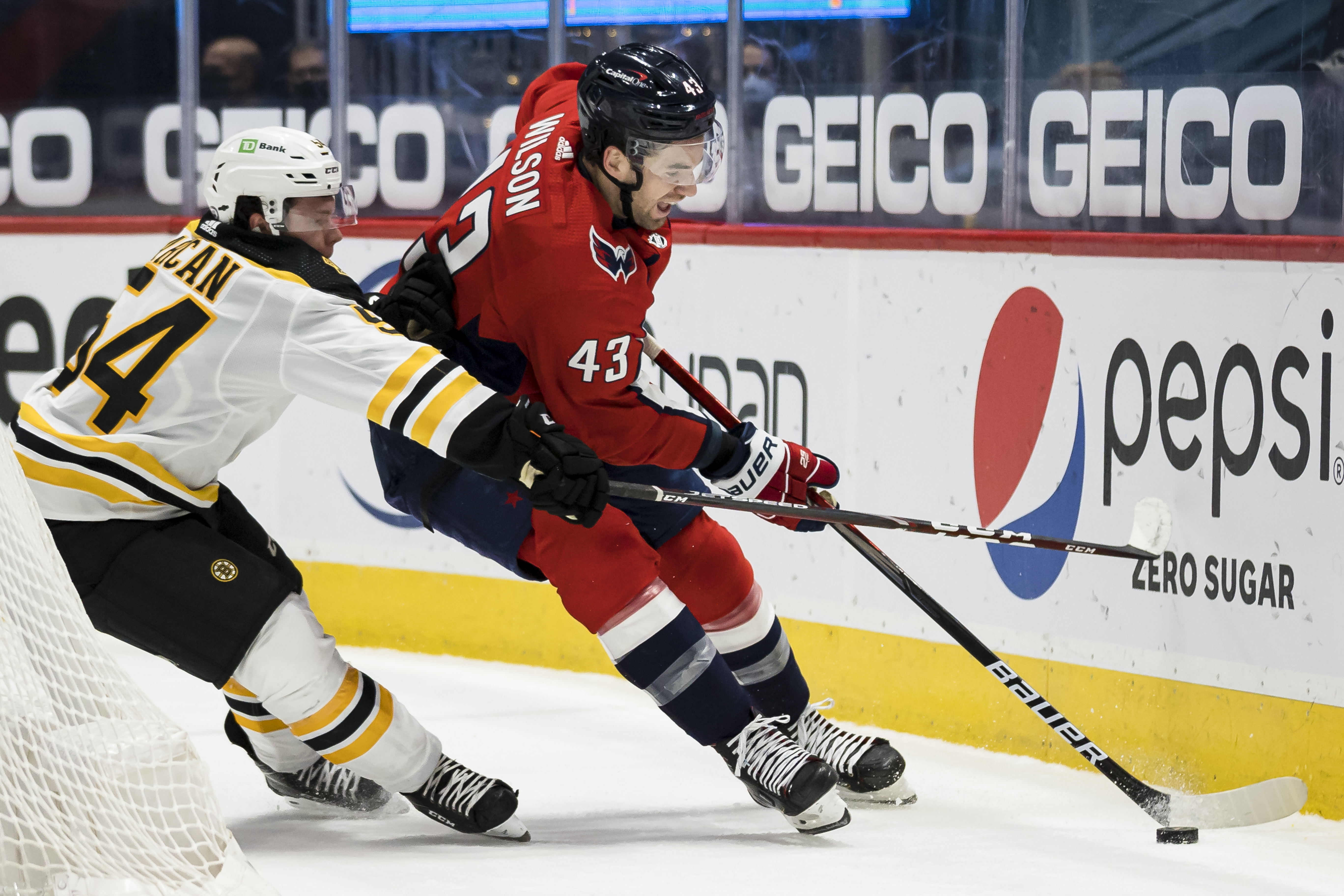 Tom Wilson #43 of the Washington Capitals skates with the puck in front of Jack Ahcan #54 of the Boston Bruins during the second period of the game at Capital One Arena on May 11, 2021 in Washington, DC.