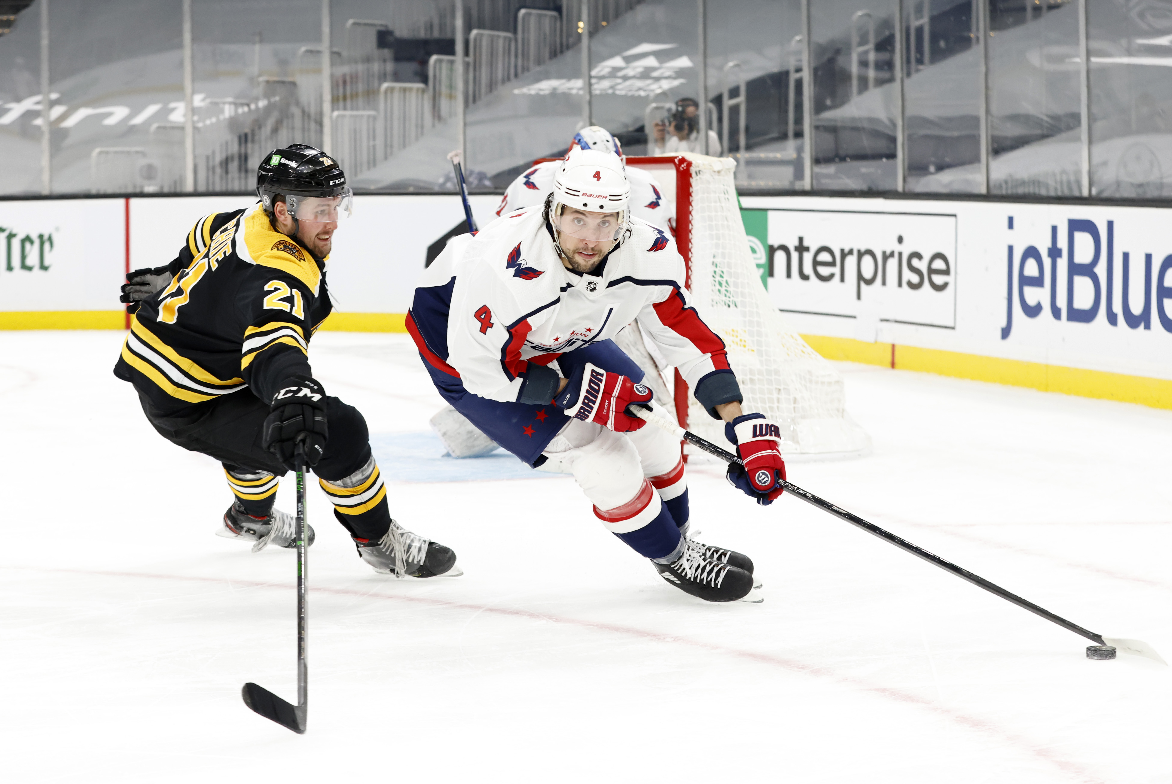 Washington Capitals defenseman Brenden Dillon (4) turns away from Boston Bruins left wing Nick Ritchie (21) during a game between the Boston Bruins and the Washington Capitals on March 3, 2021, at TD Garden in Boston, Massachusetts.
