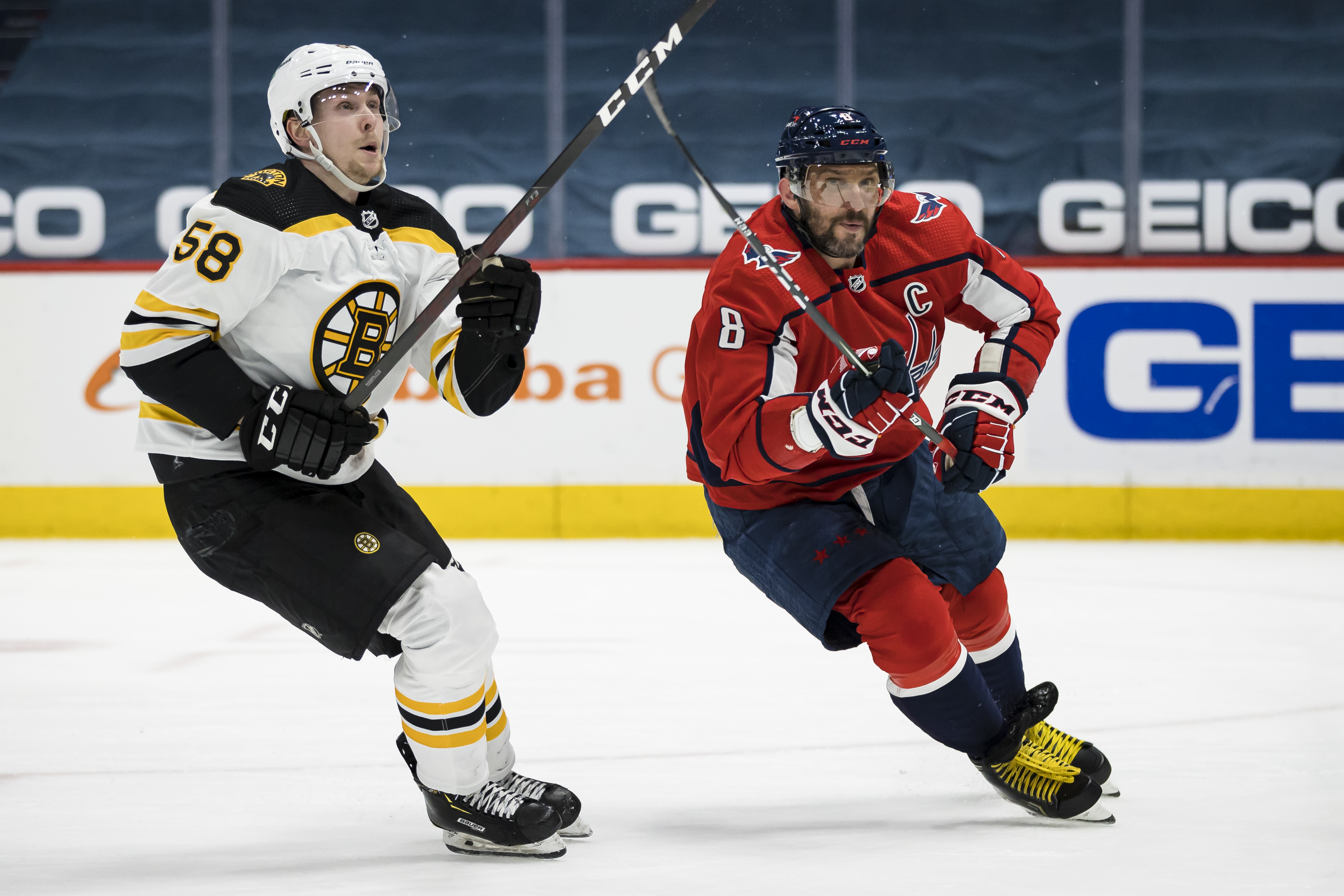 Alex Ovechkin #8 of the Washington Capitals and Urho Vaakanainen #58 of the Boston Bruins skate for a loose puck during the second period of the game at Capital One Arena on May 11, 2021 in Washington, DC.