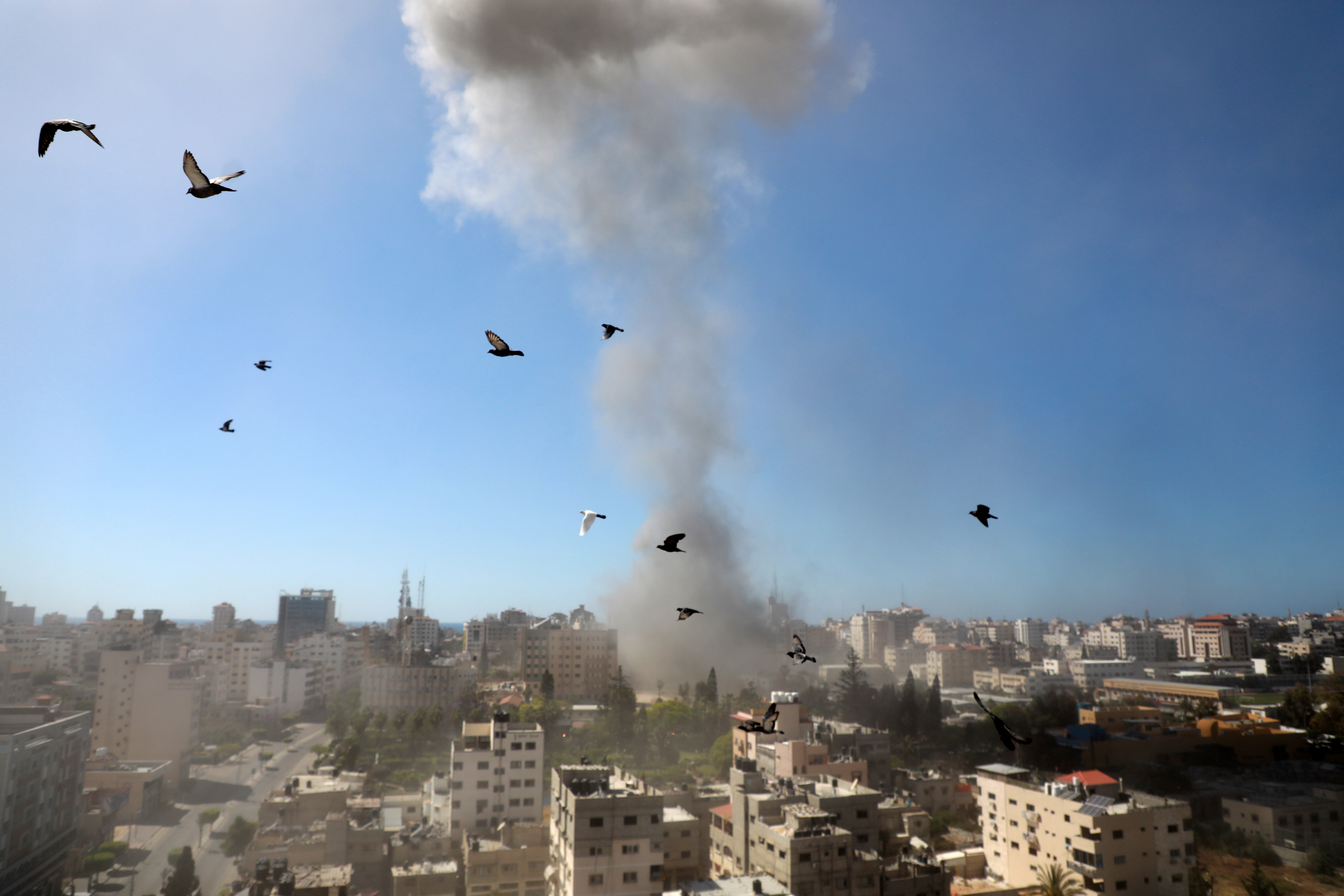 A thick column of smoke rises from the al-Jalaa Tower in Gaza as it is destroyed by an Israeli airstrike.