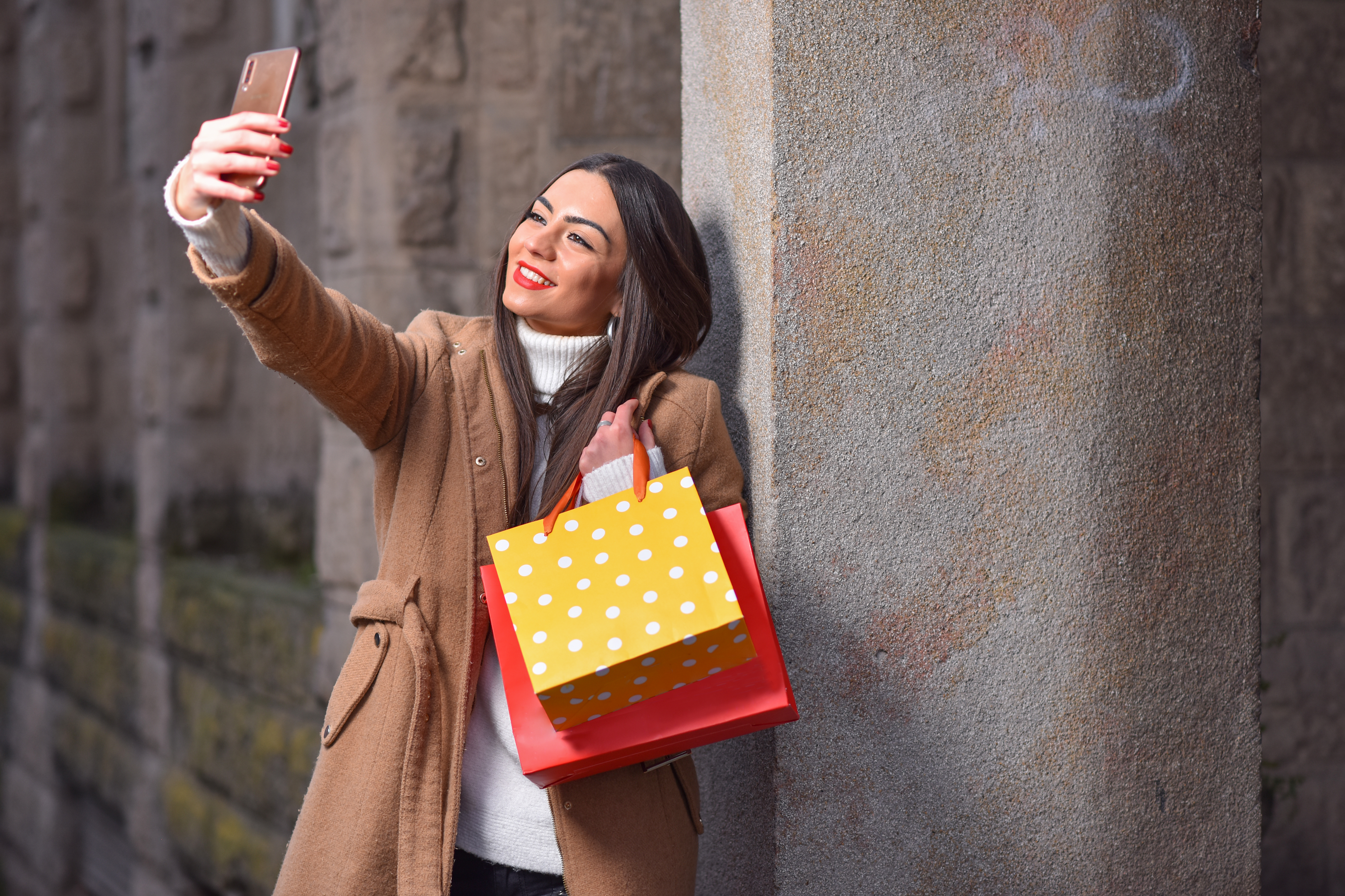 Woman taking a selfie with shopping bags.