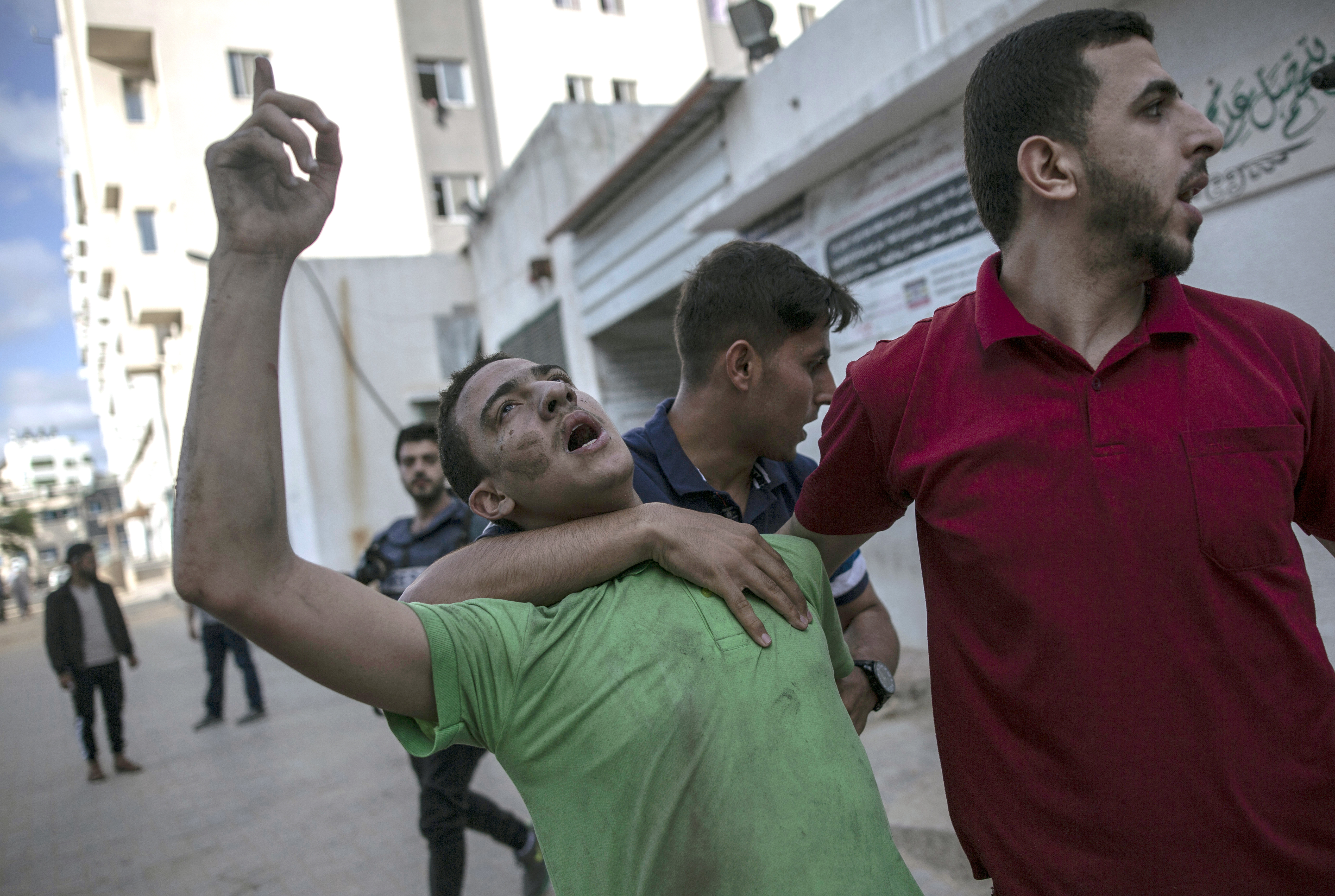 A Palestinian man reacts to the death of his father who was killed by an Israeli airstrike that destroyed the upper floors of a commercial building and caused damage to the nearby Health Ministry and prime health care clinic, in Gaza City, Monday, May 17, 2021.