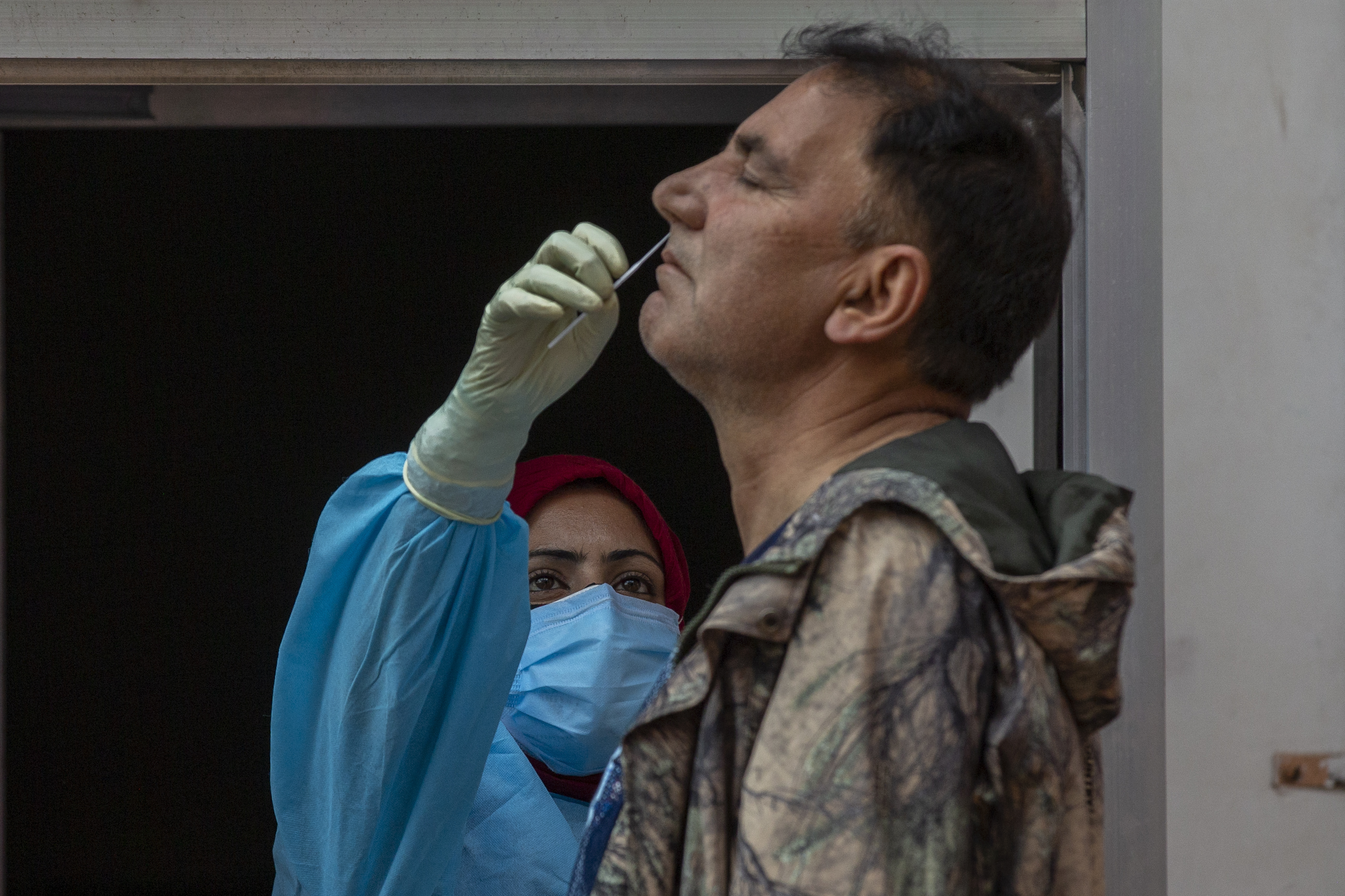 In this May 11, 2021 file photo, a health worker takes a nasal swab sample of a Kashmiri man to test for COVID-19 in Srinagar, Indian controlled Kashmir. A dip in the number of coronavirus cases in Mumbai is offering a glimmer of hope for India, which is suffering through a surge of infections.