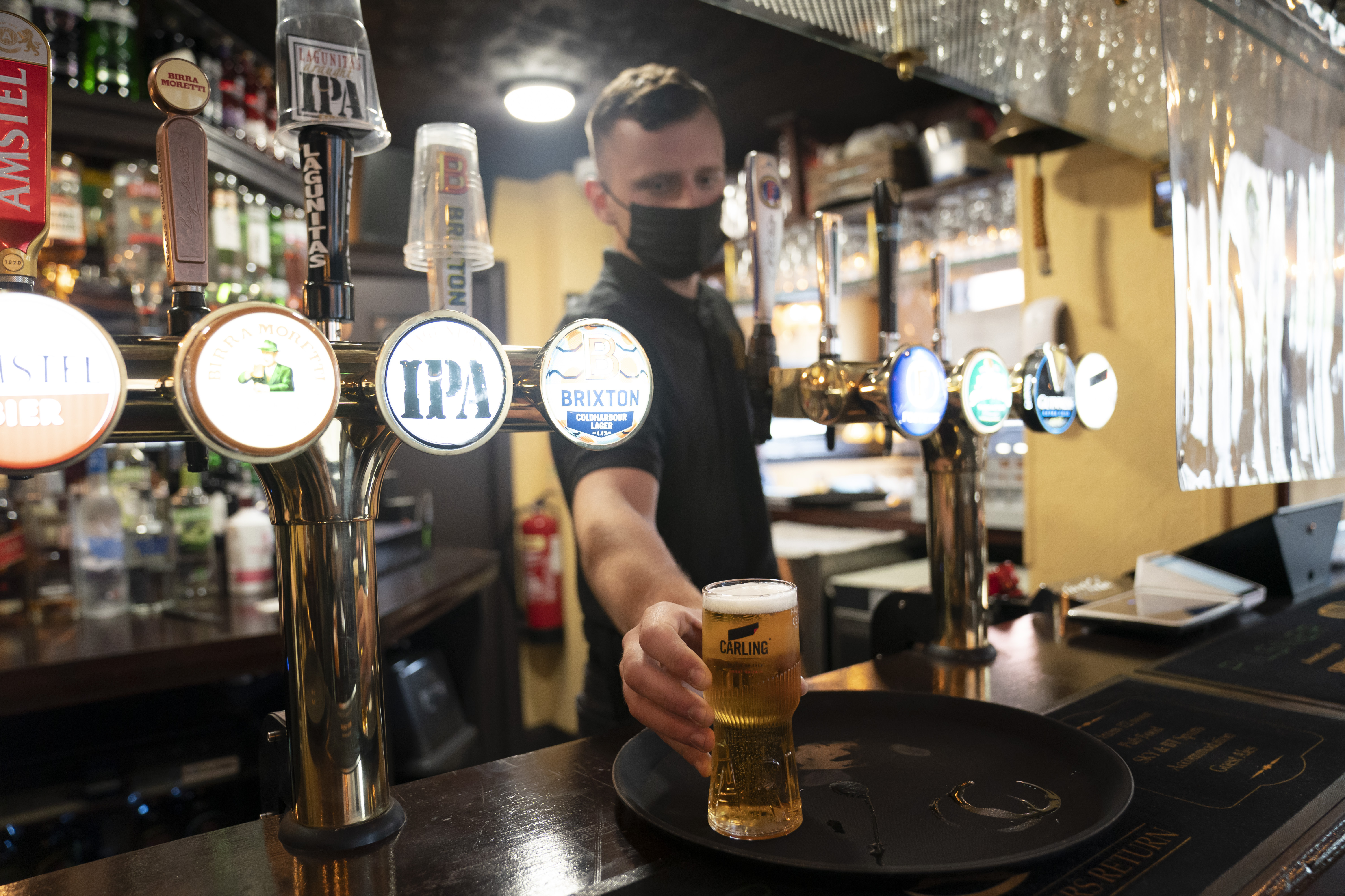 A member of staff serves a drink, as pubs, cafes and restaurants in England reopen indoors under the latest easing of the coronavirus lockdown, in Manchester, England, Monday, May 17, 2021.