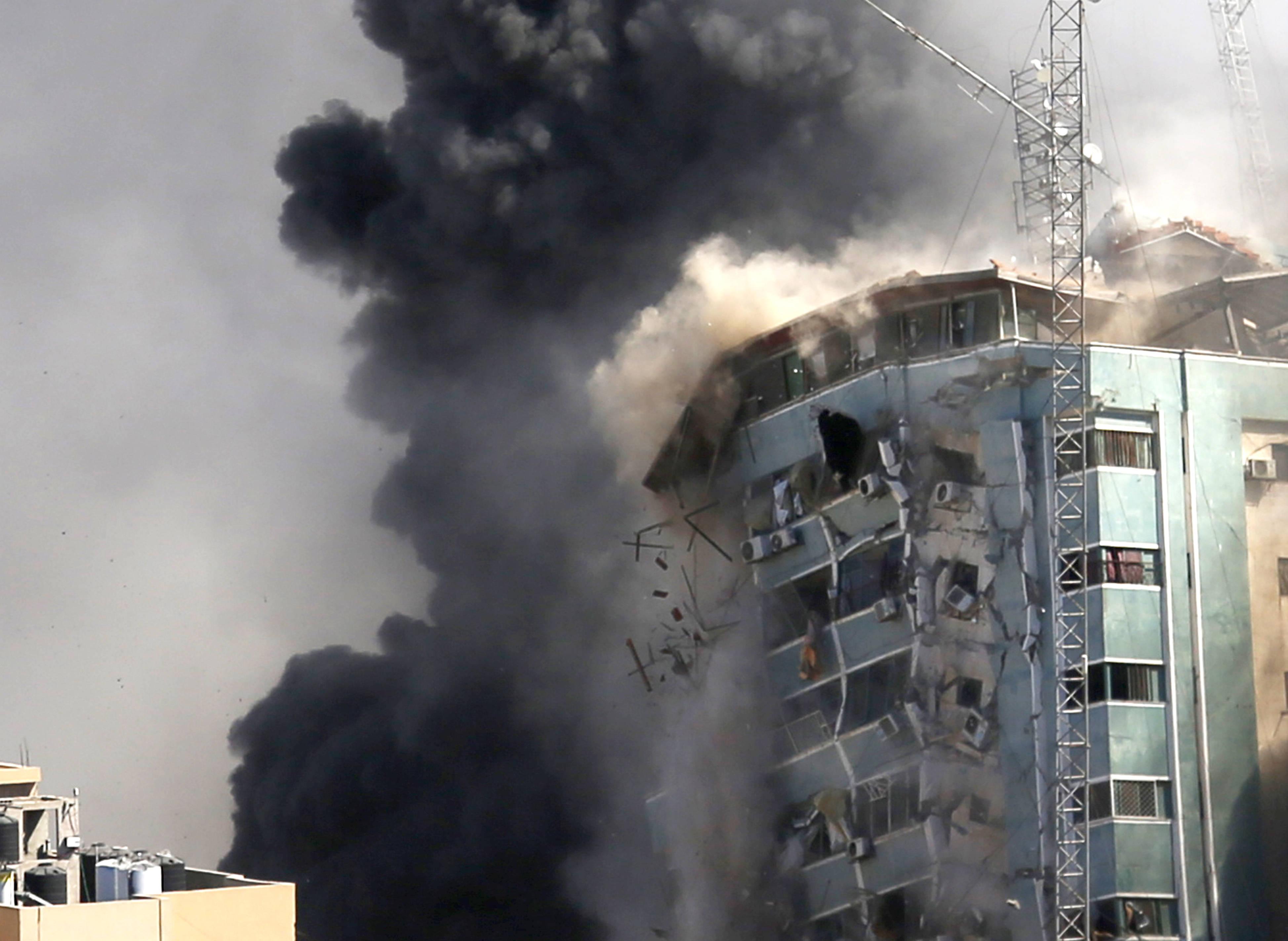 The building housing the offices of The Associated Press and other media in Gaza City collapses after it was hit by an Israeli airstrike Saturday, May 15, 2021.