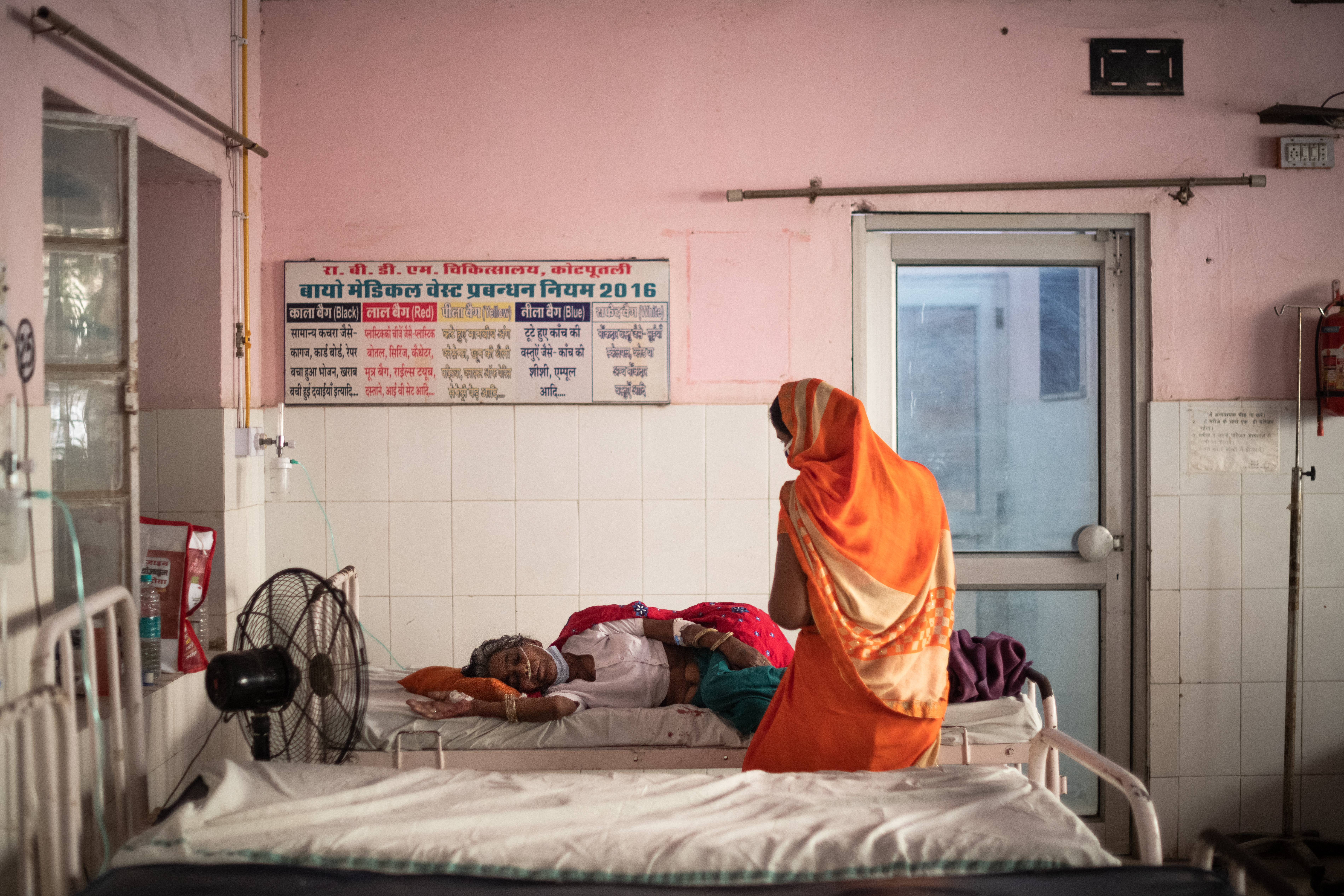 A visitor wearing a sari sits on a bed beside a patient receiving oxygen at a hospital in India.