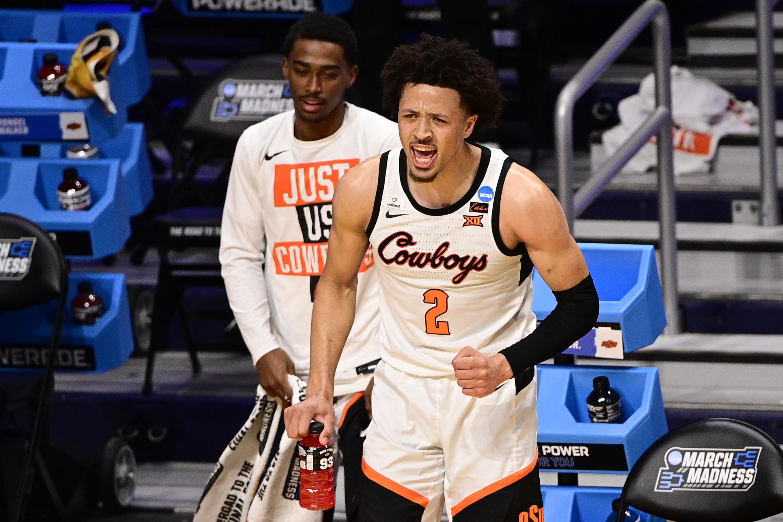 在Hinkle Fieldhouse球场举行的2021年NCAA锦标赛第二轮比赛中,俄克拉荷马州立牛仔队后卫凯德·坎宁安在边线上呐喊。