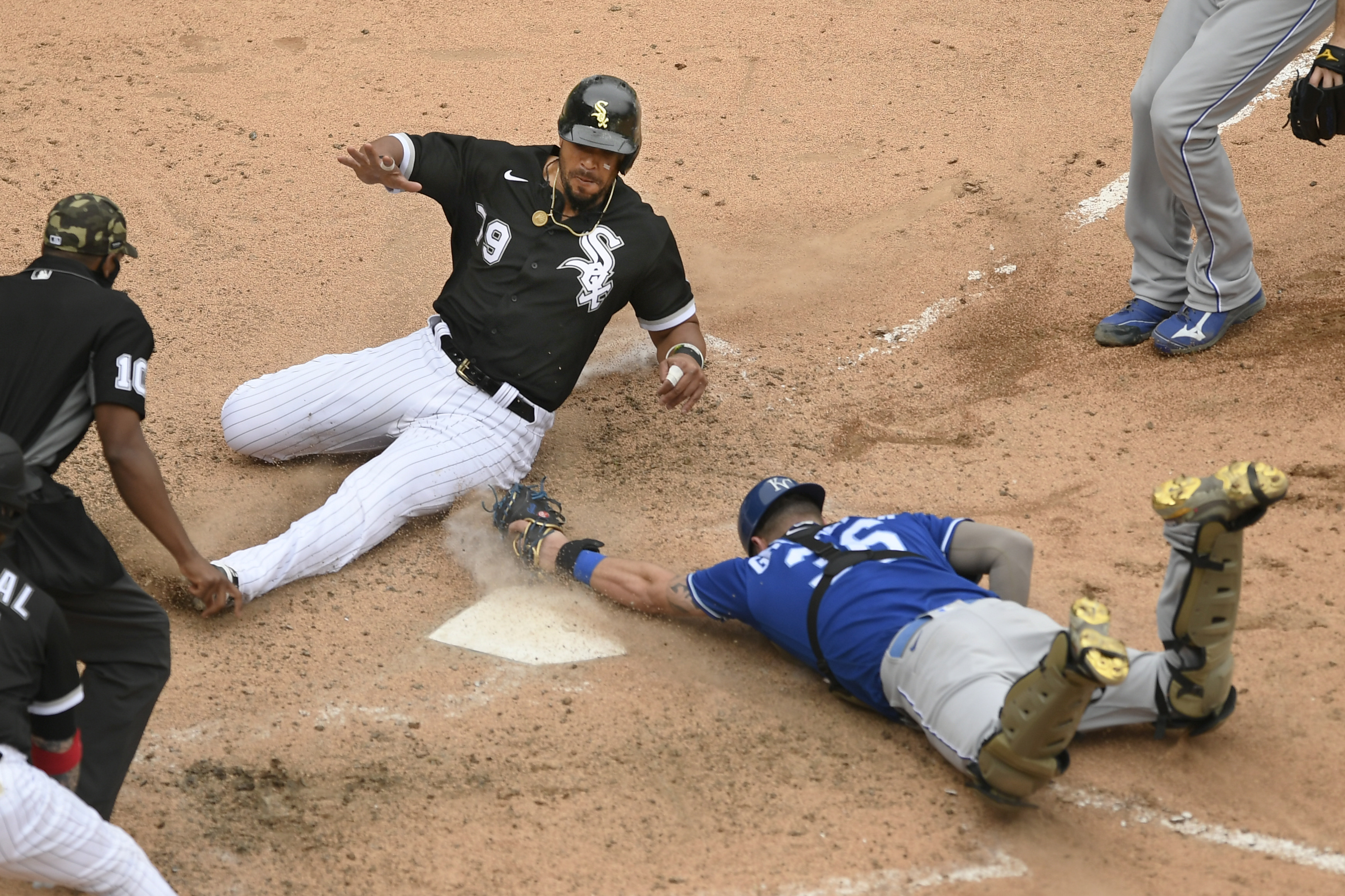 The White Sox' Jose Abreu slides safely into home plate while Royals catcher Cam Gallagher attempts to apply the tag during the ninth inning of Sunday's game.