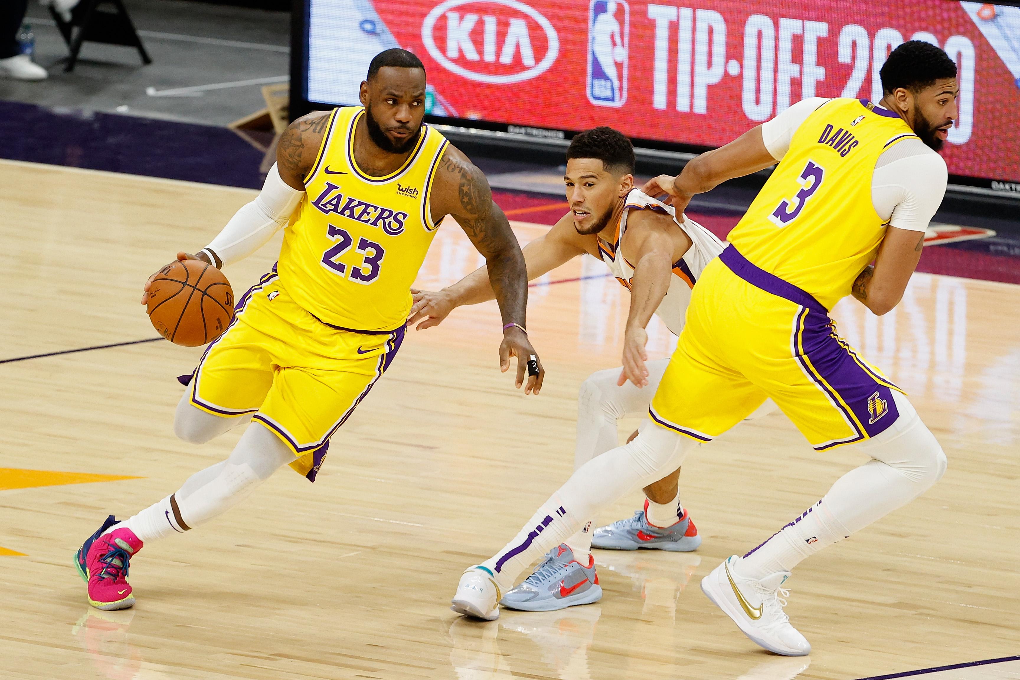 2020年12月18日,美国亚利桑那州菲尼克斯,洛杉矶湖人队勒布朗·詹姆斯在NBA季前赛上半场安东尼·戴维斯挡下了菲尼克斯太阳队的德文·布克。