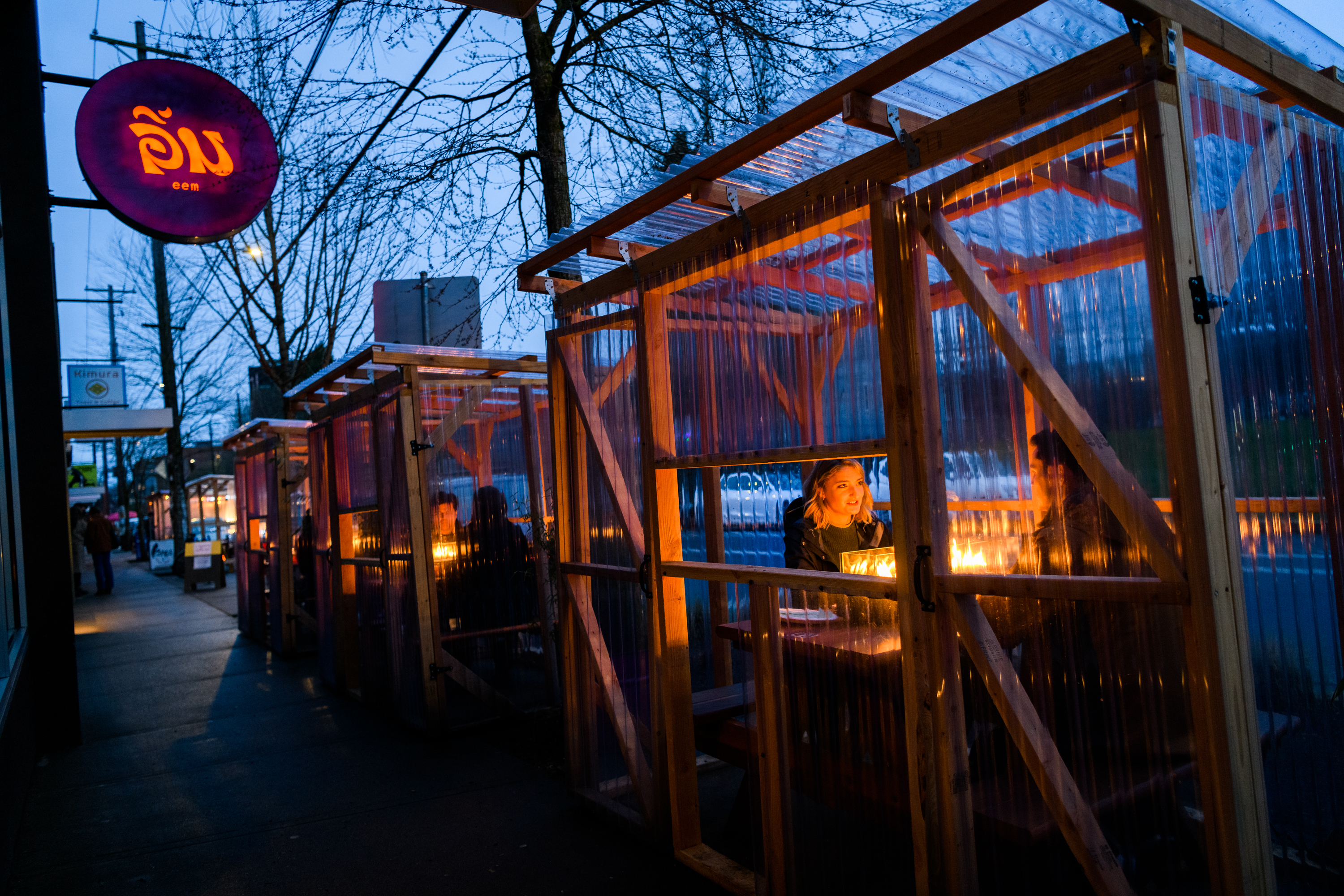 Along the sidewalk outside Eem, little greenhouse-style pods lined with plastic house single tables for customers to use.