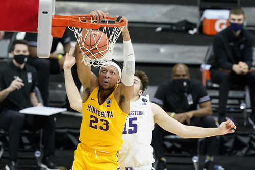Minnesota's Brandon Johnson (23) dunks against Northwestern's Ryan Young (15) during the first half of an NCAA college basketball game at the Big Ten Conference tournament.