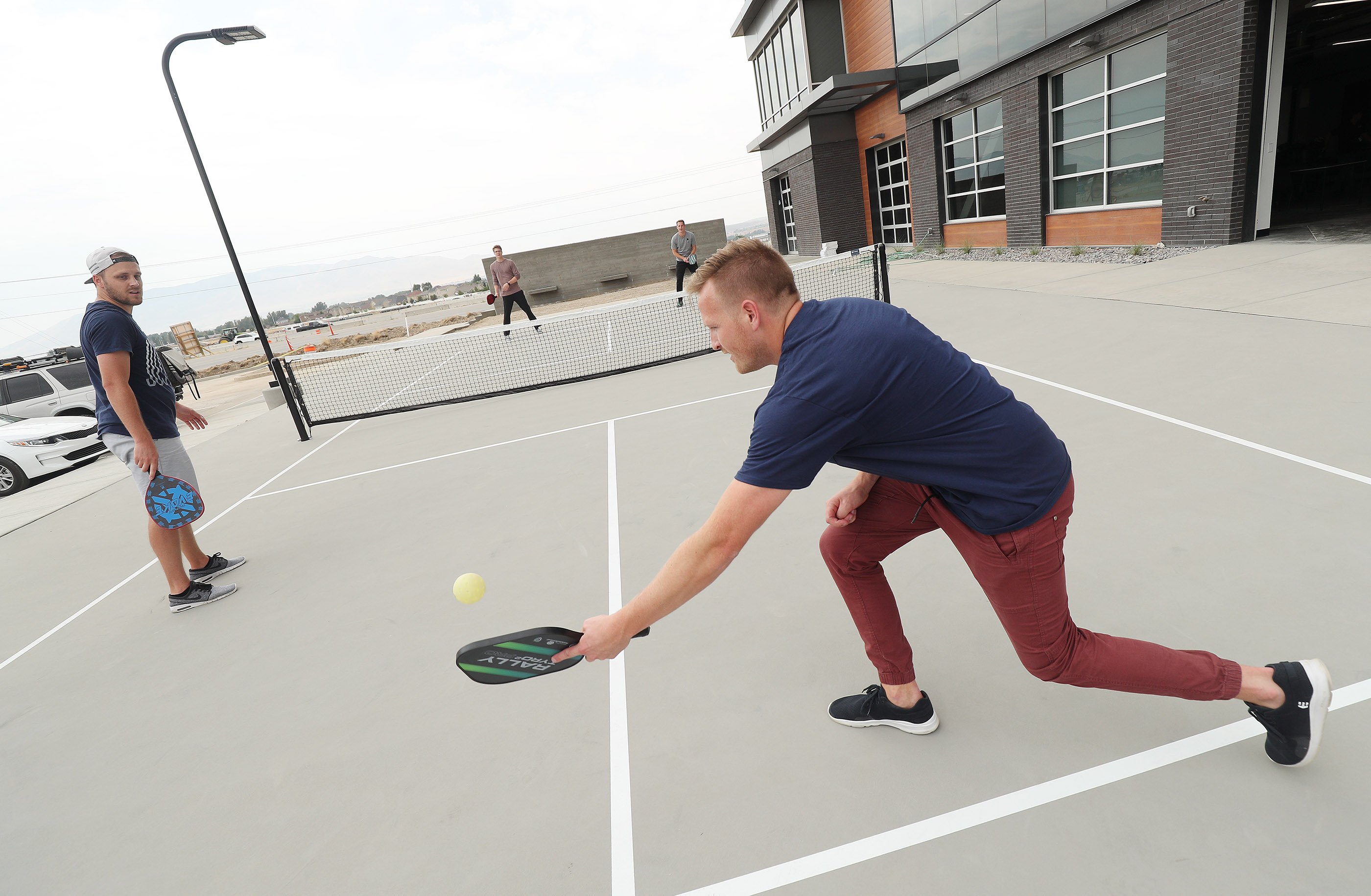 Regan Bushman hits the ball to a co-worker during a game of pickleball at Podium in Lehi.