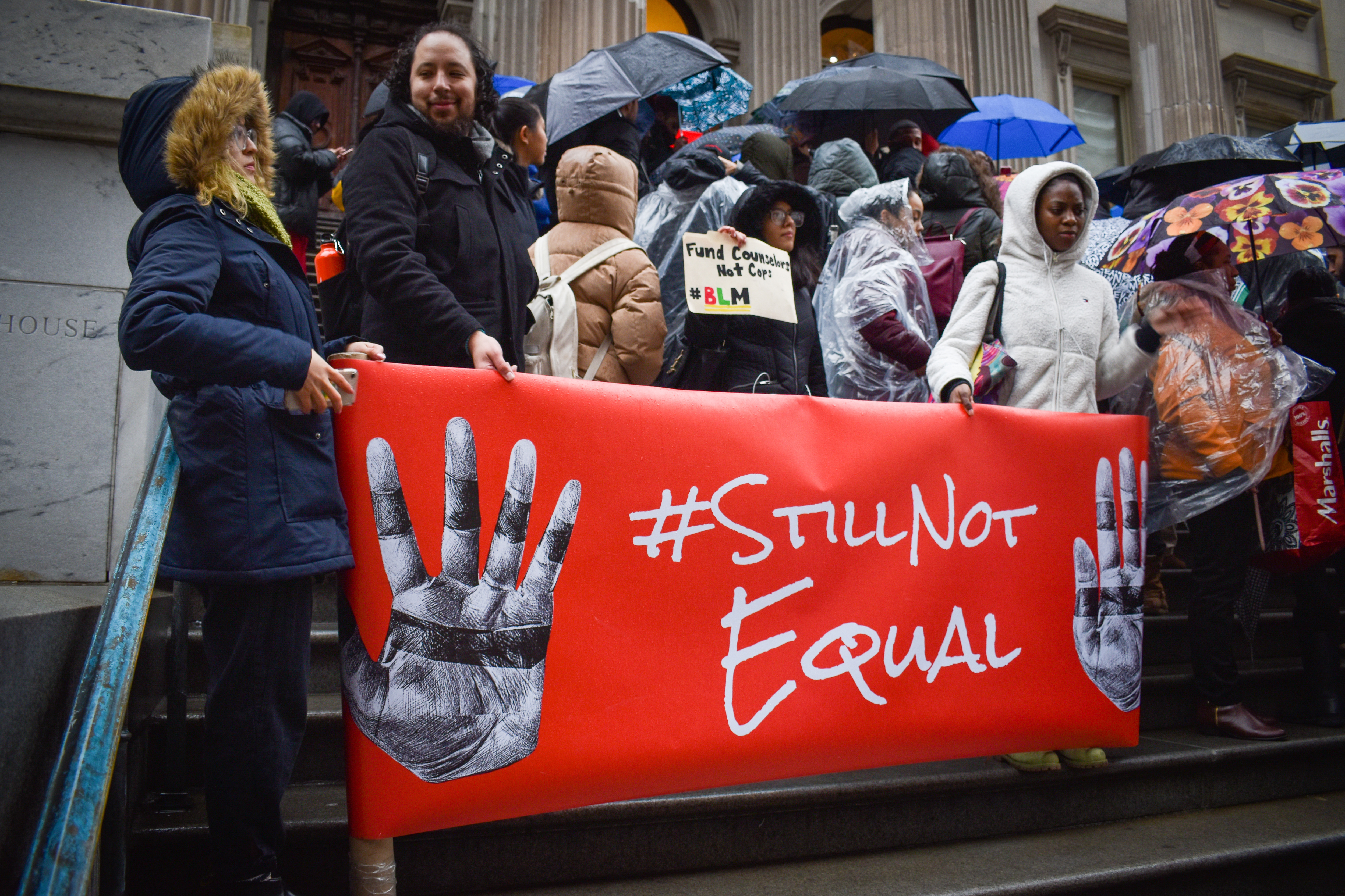 """A group of people hold a red sign that says """"Still Not Equal."""""""