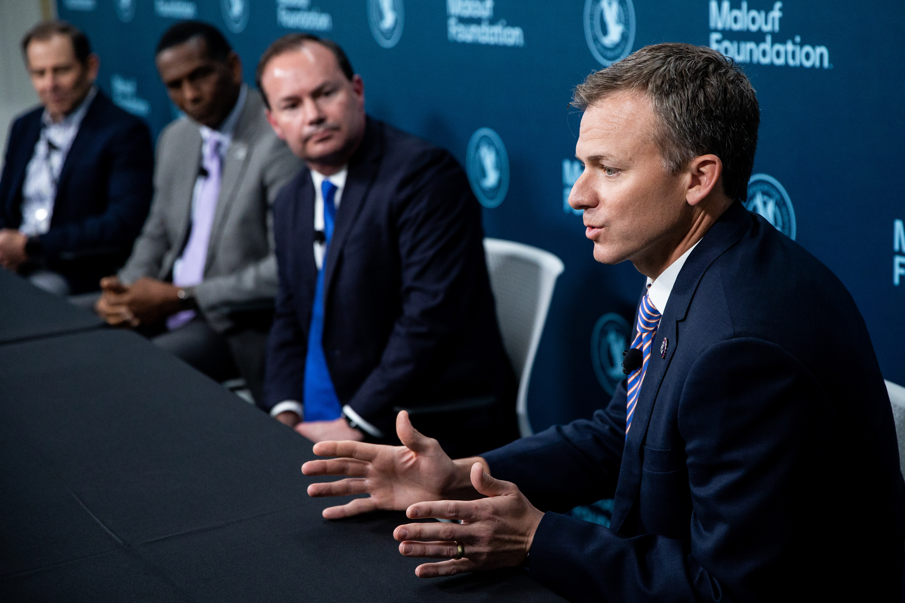 Utah Rep. Blake Moore, seated next to Sen. Mike Lee, Rep. John Curtis and Rep. Burgess Owens, gestures while talking at the Human Trafficking Policy and Education Summit in April 2021.