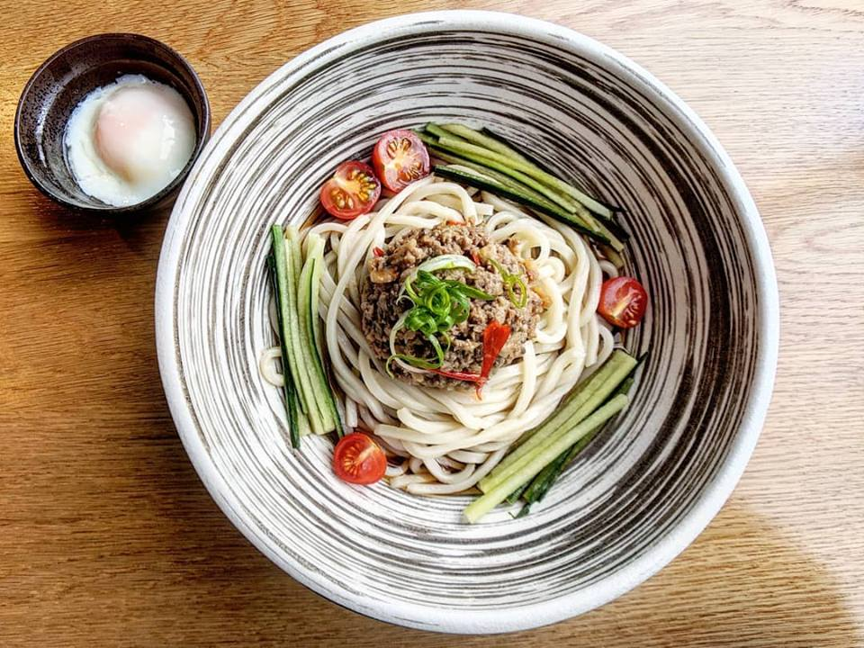 An eye-catching black-and-white striped bowl is full of a brothless udon garnished with sliced tomatoes, cucumbers, scallions, and ground meat