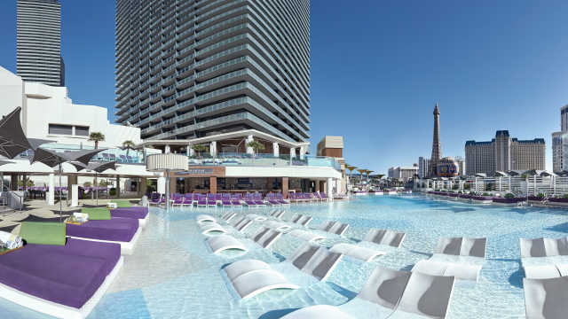 A pool with cabanas and a hotel in the background