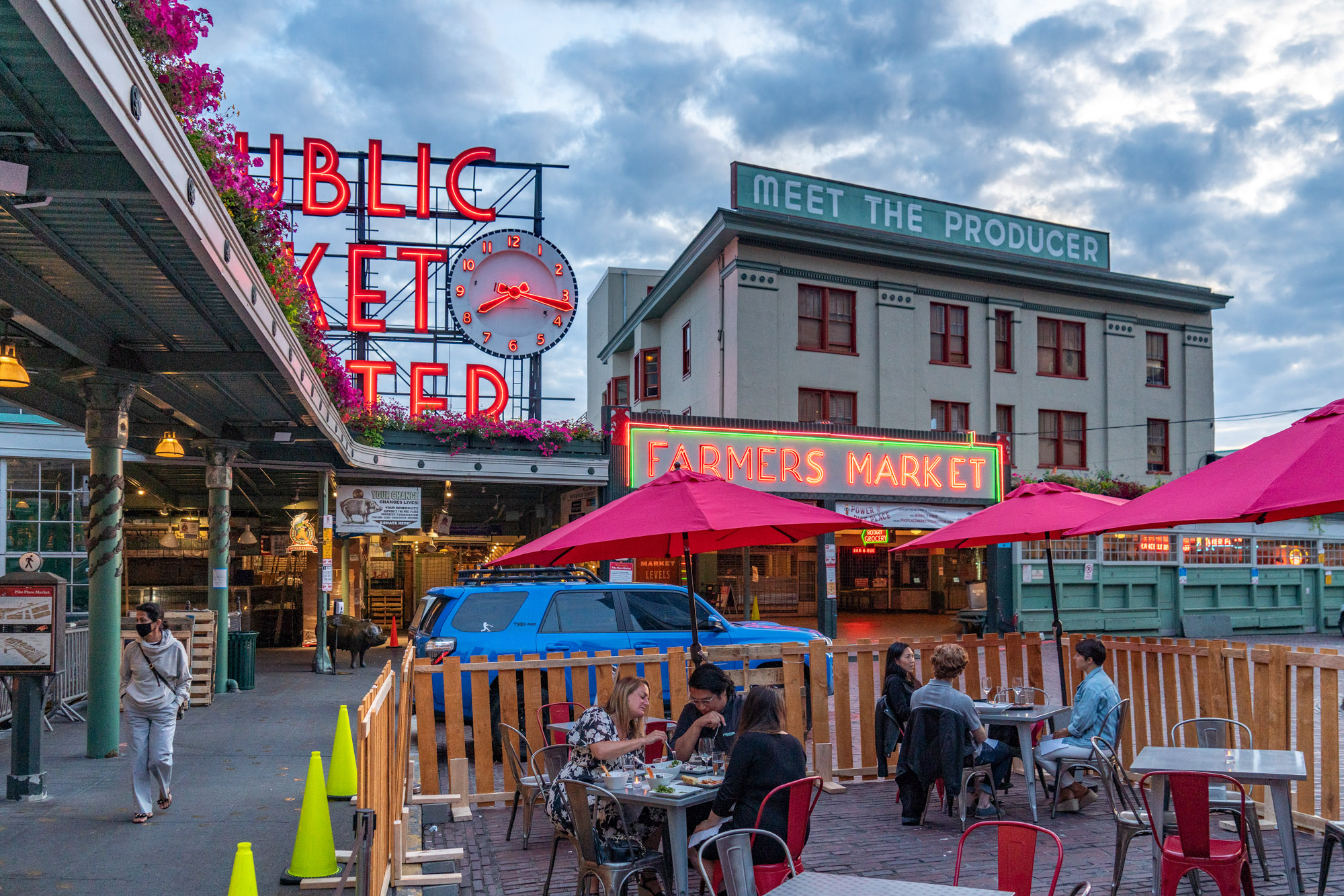 Outdoor seating around Pike Place Market, with the market's famed sign in the background and pink umbrellas displayed around tables filled with patrons