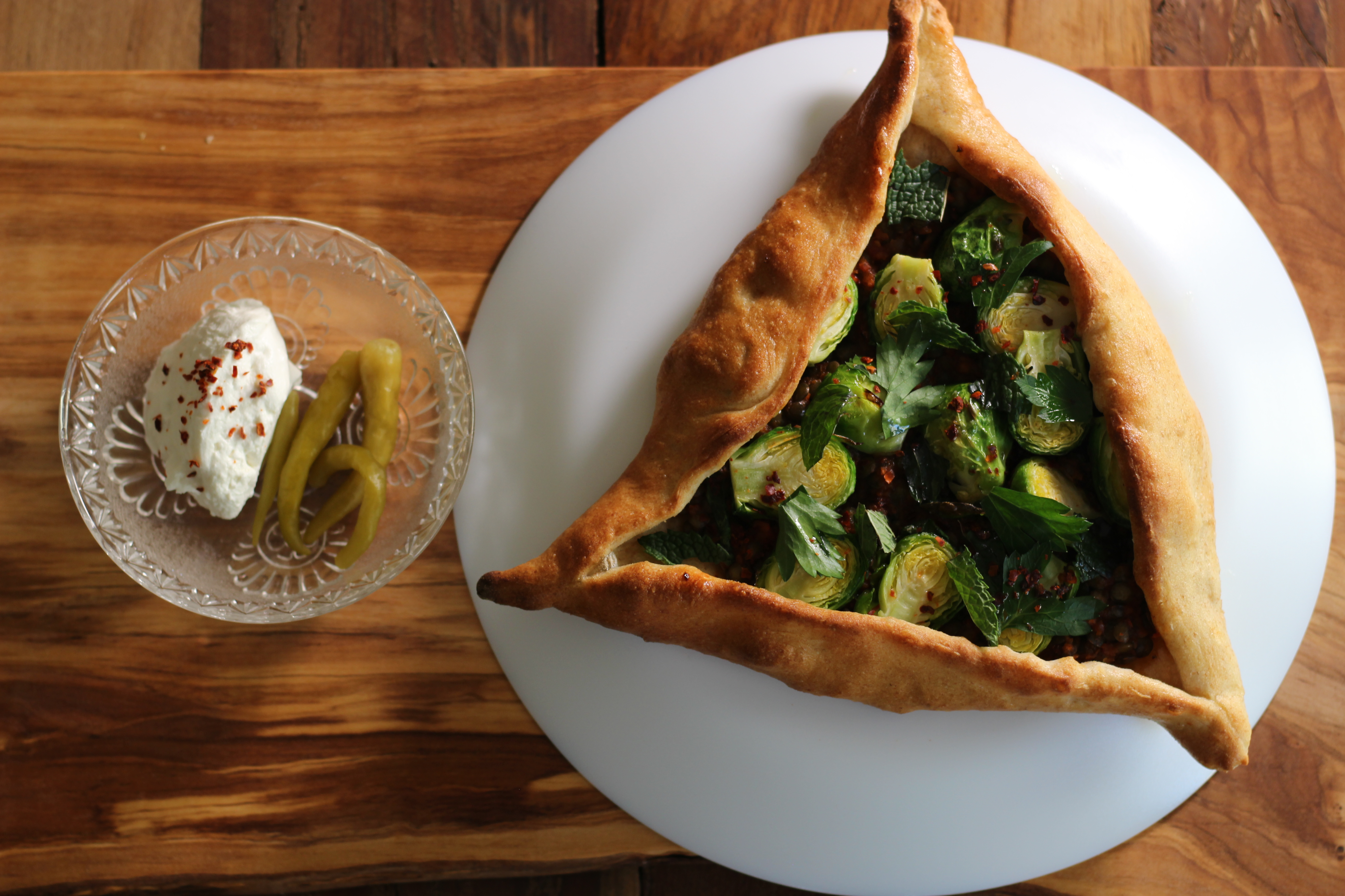 Overhead view of a triangular hand pie stuffed with Brussels sprouts. On the side, there's a small clear bowl with a scoop of a thick white sauce and a pickled garnish.