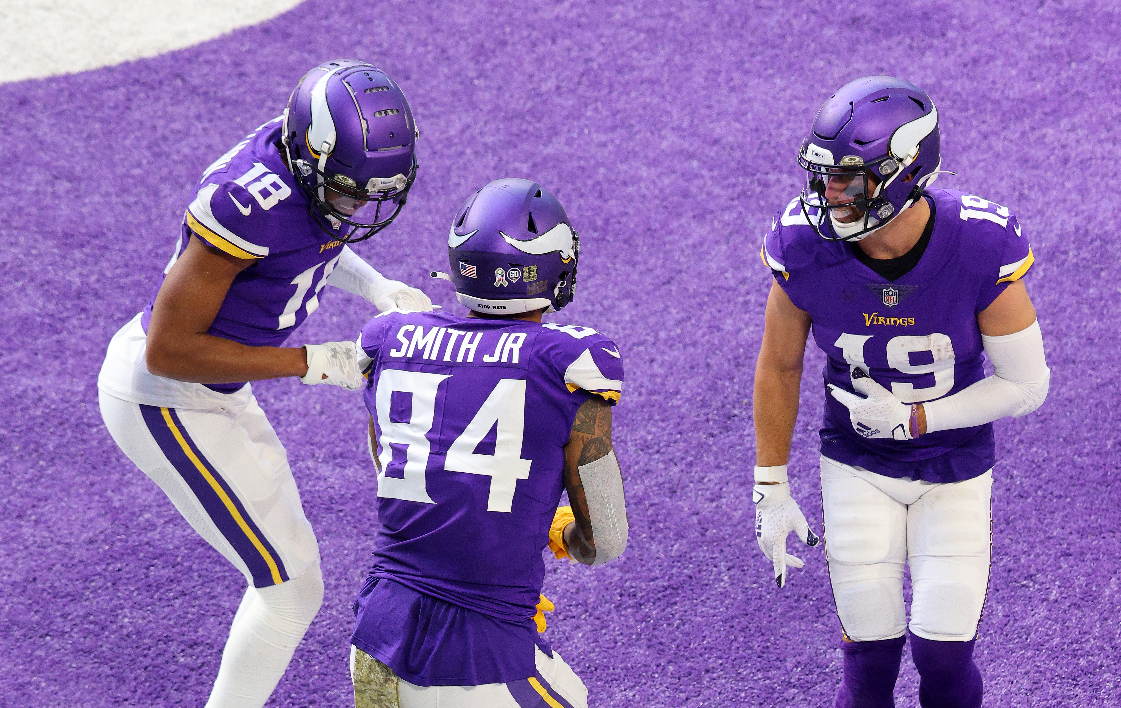 Irv Smith Jr. #84 of the Minnesota Vikings celebrates with Justin Jefferson #18 and Adam Thielen #19 after he scored a touchdown against the Detroit Lions at U.S. Bank Stadium on November 08, 2020 in Minneapolis, Minnesota.