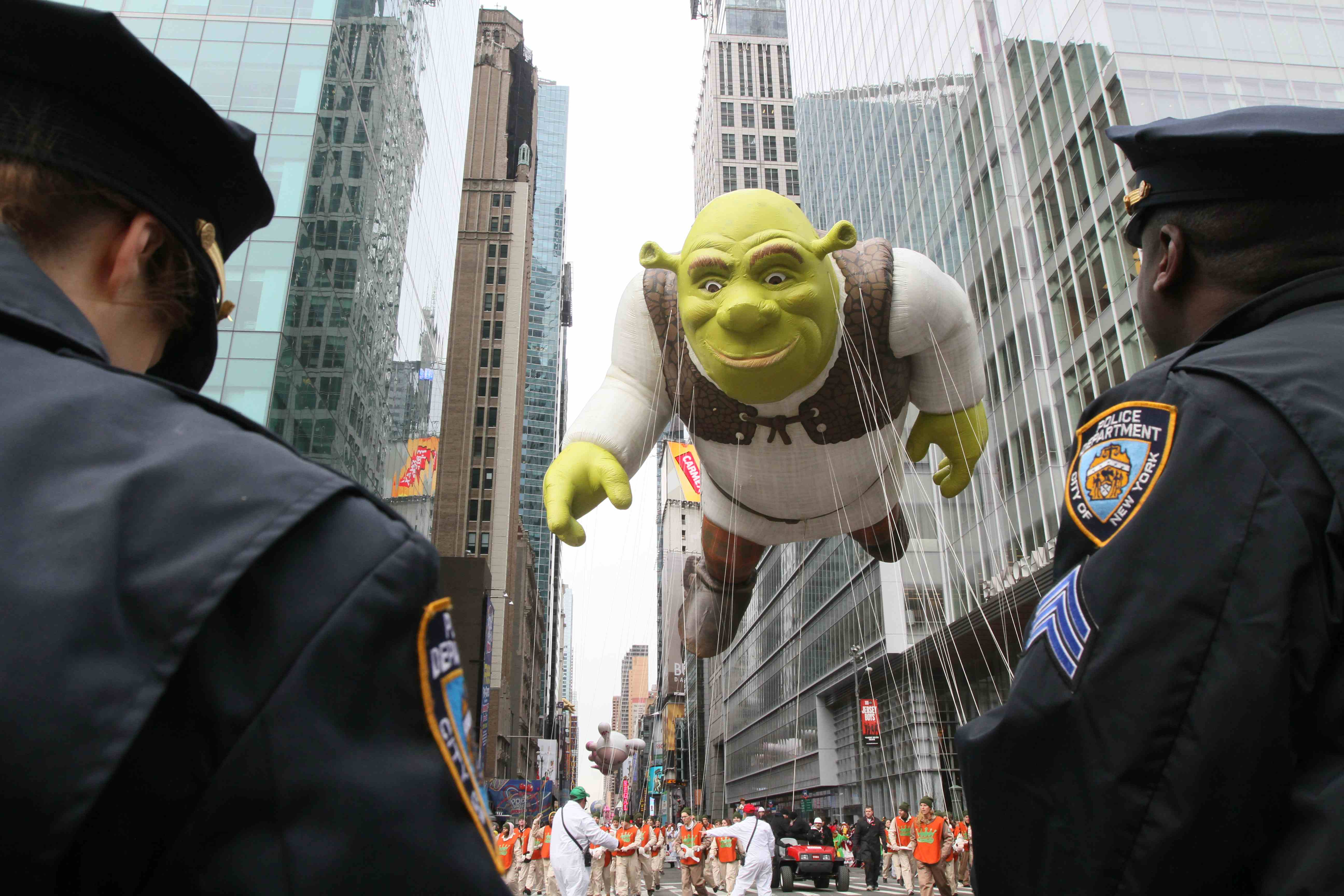 Members of the New York Police Department stand by as the Shrek balloon at the Macy's Thanksgiving Day Parade.