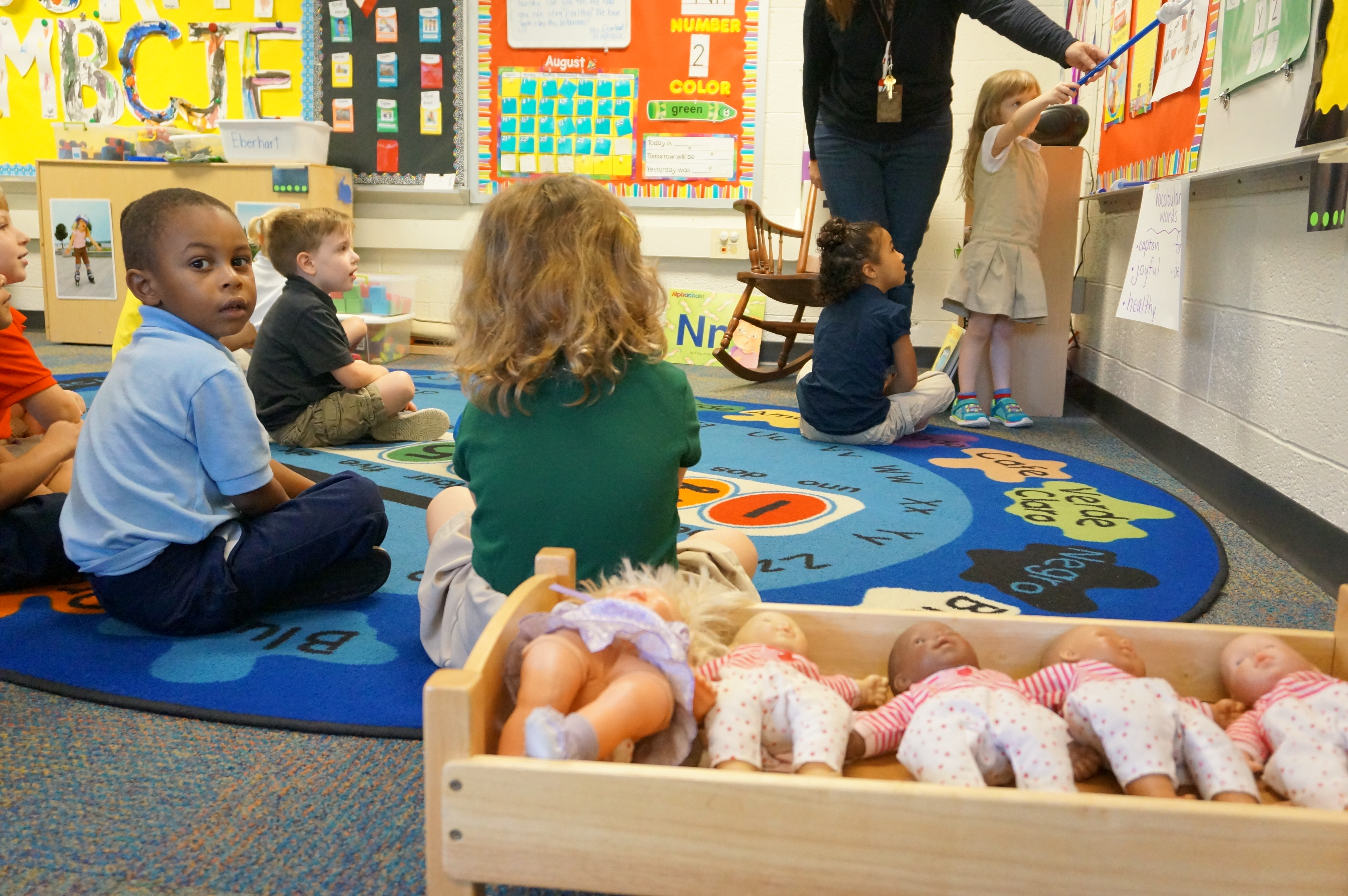 A group of six preschoolers participate in an exercise while a boy in a blue shirt looks back at the photographer. There is a row of dolls sitting in a wooden bin in the foreground.