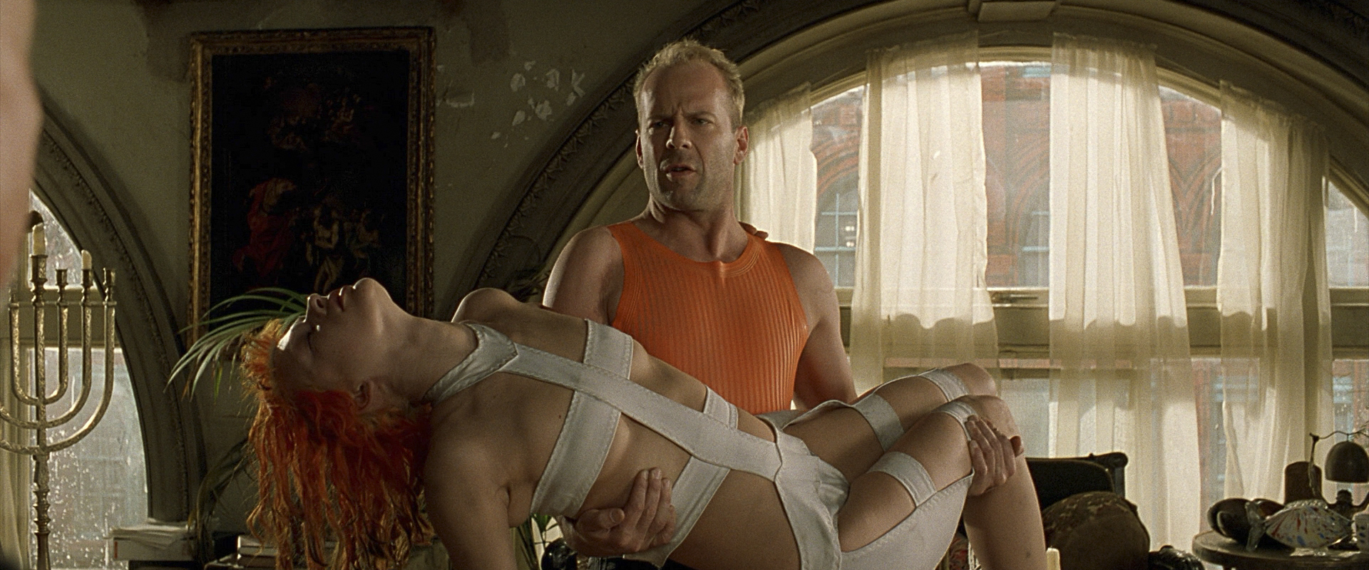 Bruce Willis in a sleeveless orange top holds Milla Jovovich in a bandage dress in The Fifth Element