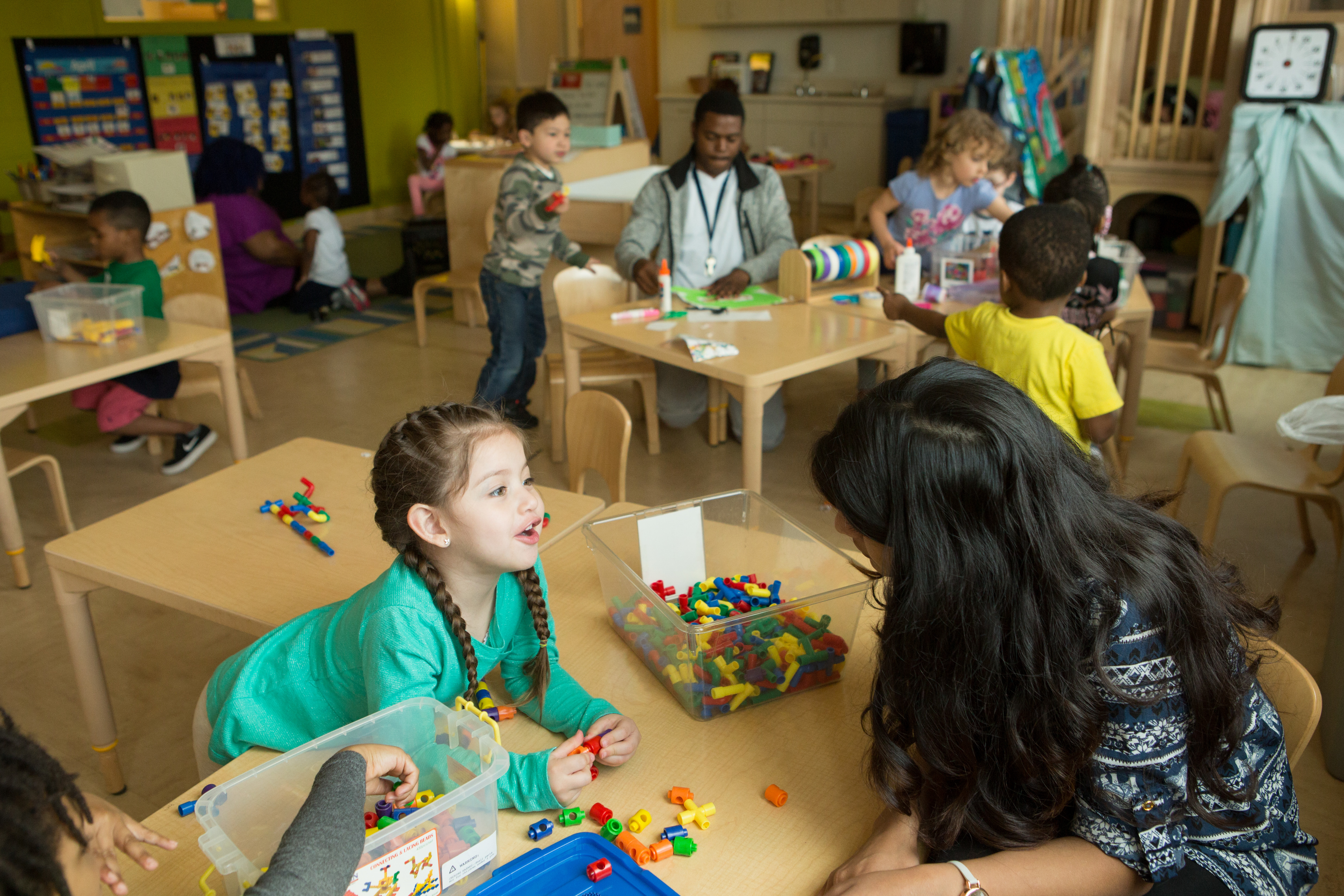 In a preschool class, a girl wearing a green shirt and pigtail braids leans over a desk, where there's a bin full of building blocks, to talk to a woman who also leans in to listen.