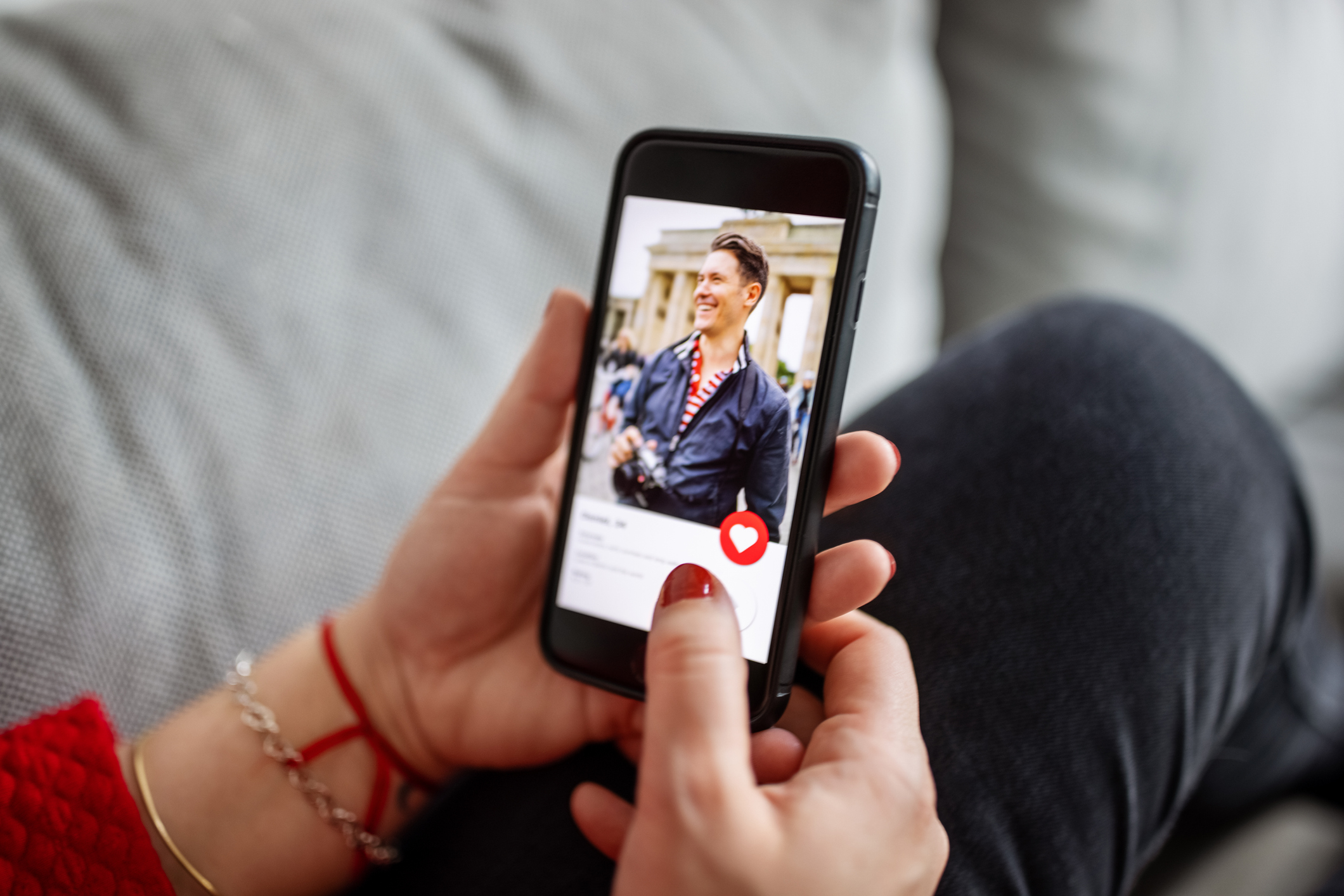 Hands holding a phone displaying a picture of a person in a dating app.