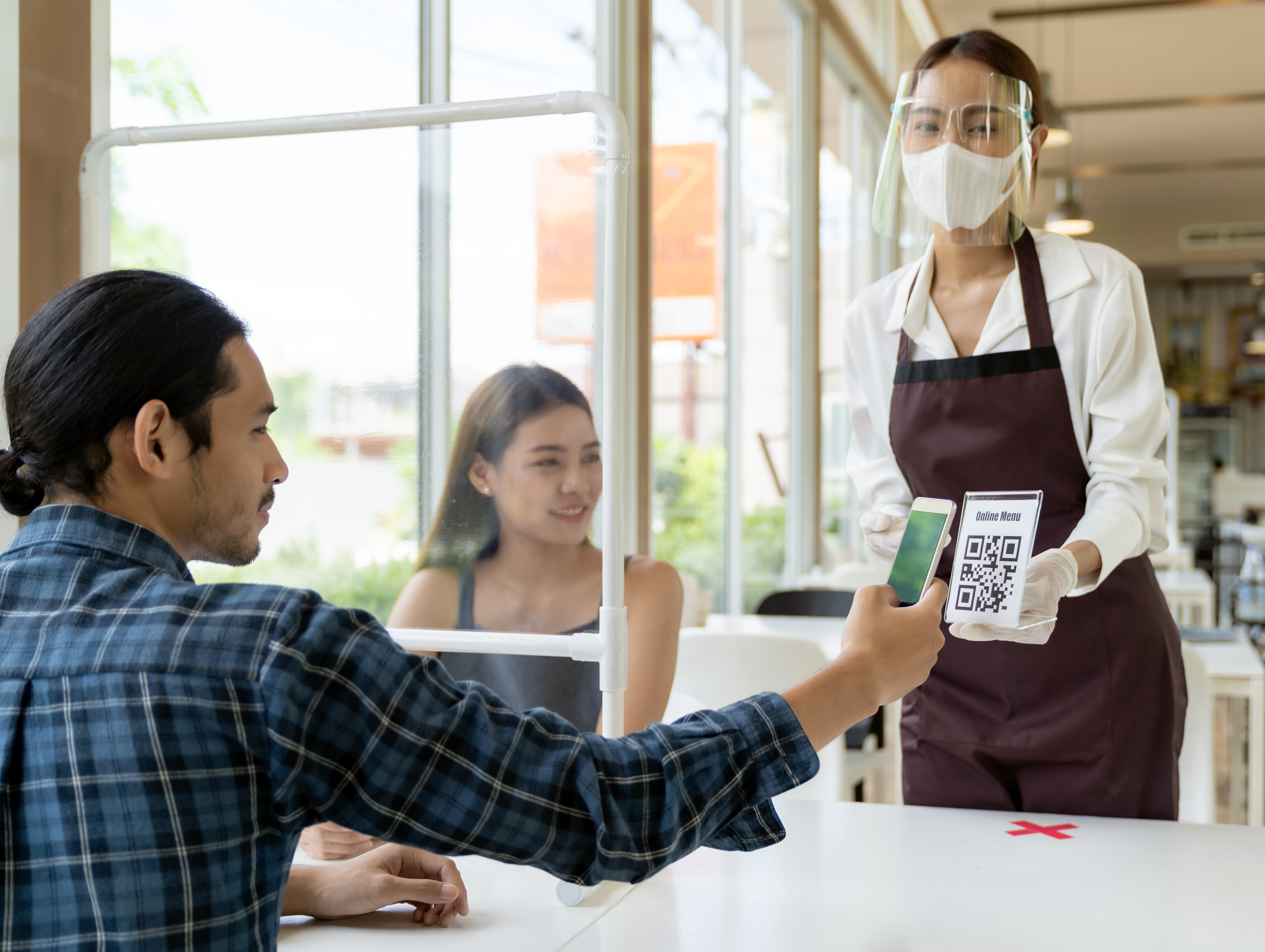 A man holds up his cellphone to a QR code held by a masked woman in a restaurant